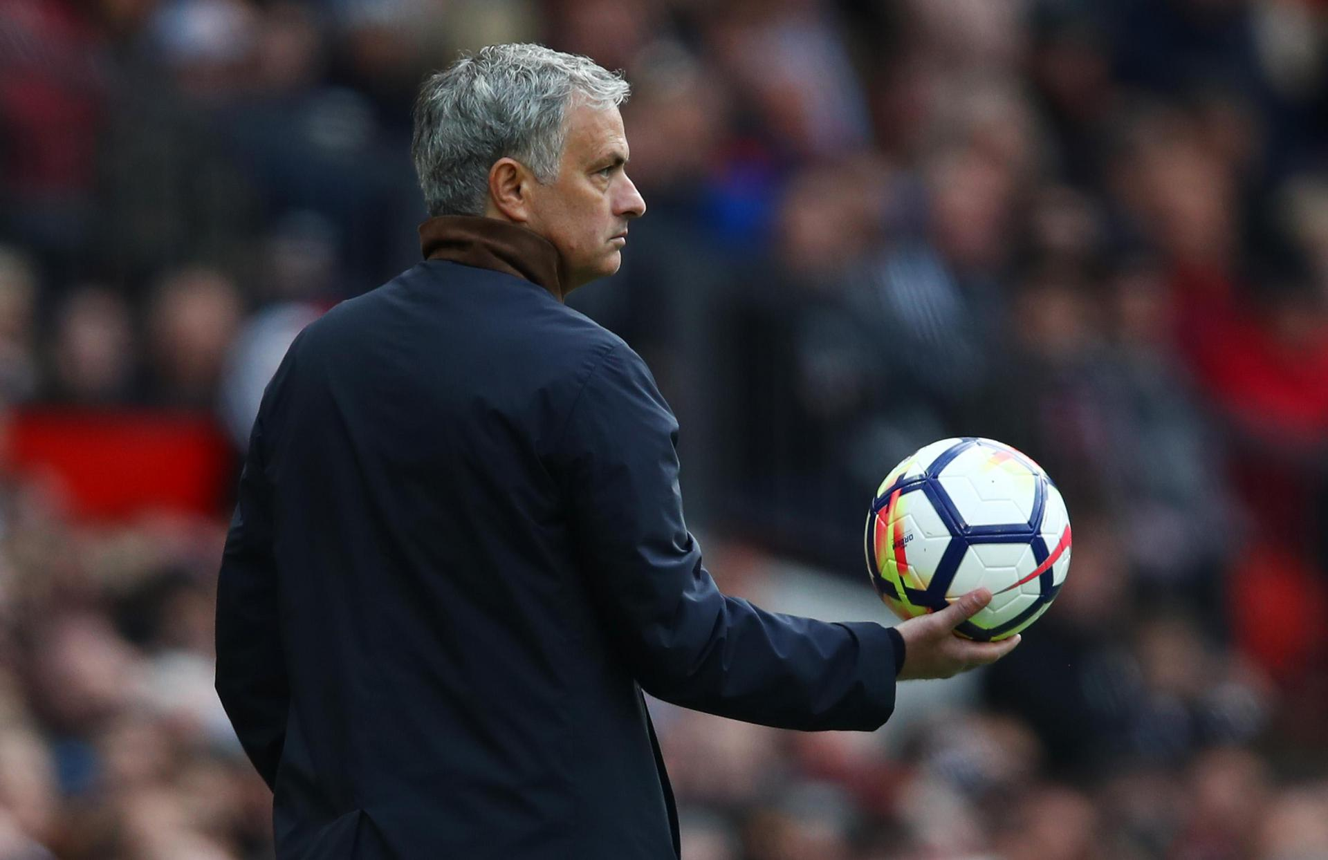 Jose Mourinho holding the ball on the touchline at Old Trafford