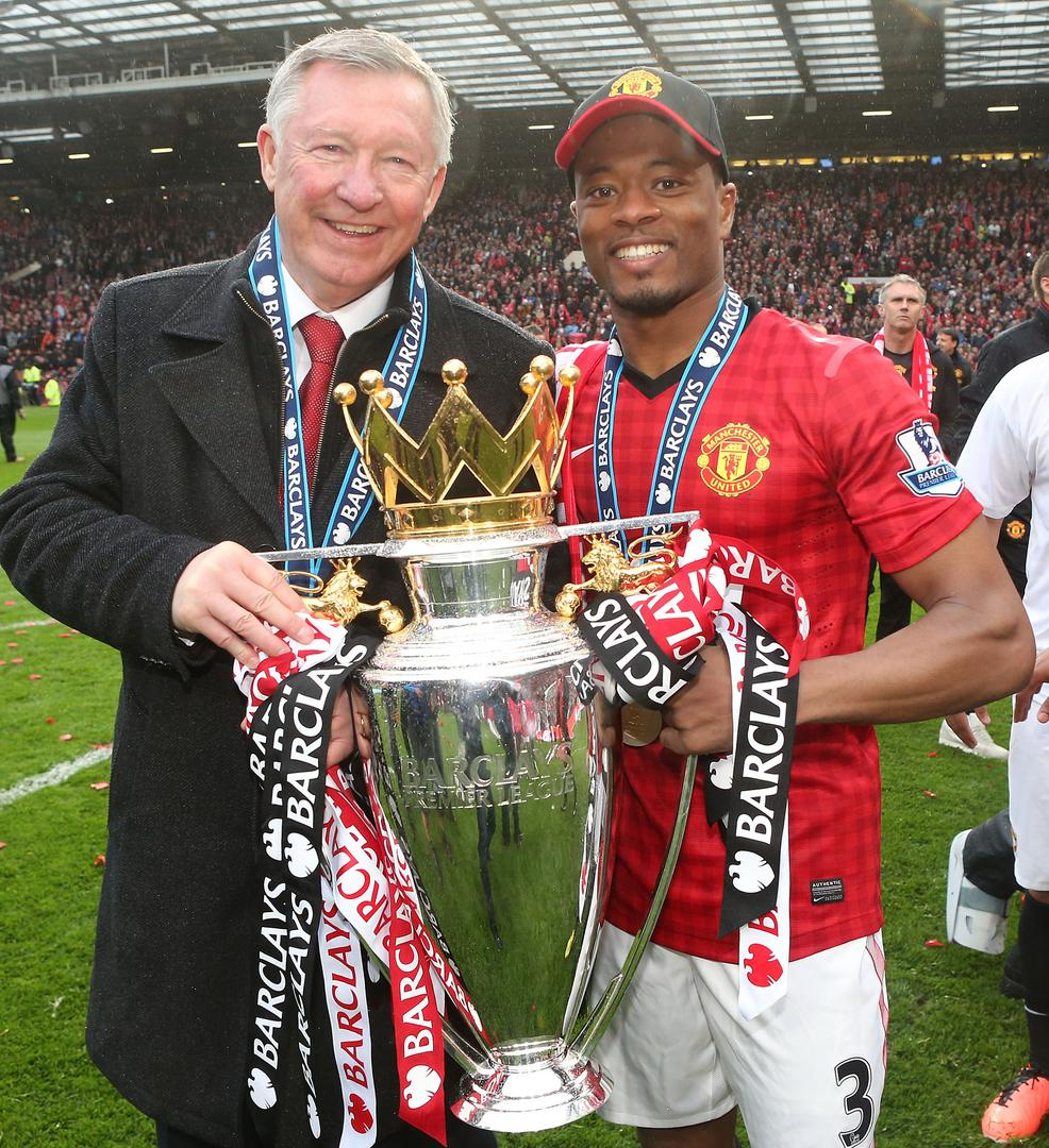 Sir Alex Ferguson and Patrice Evra holding the Premier League trophy.