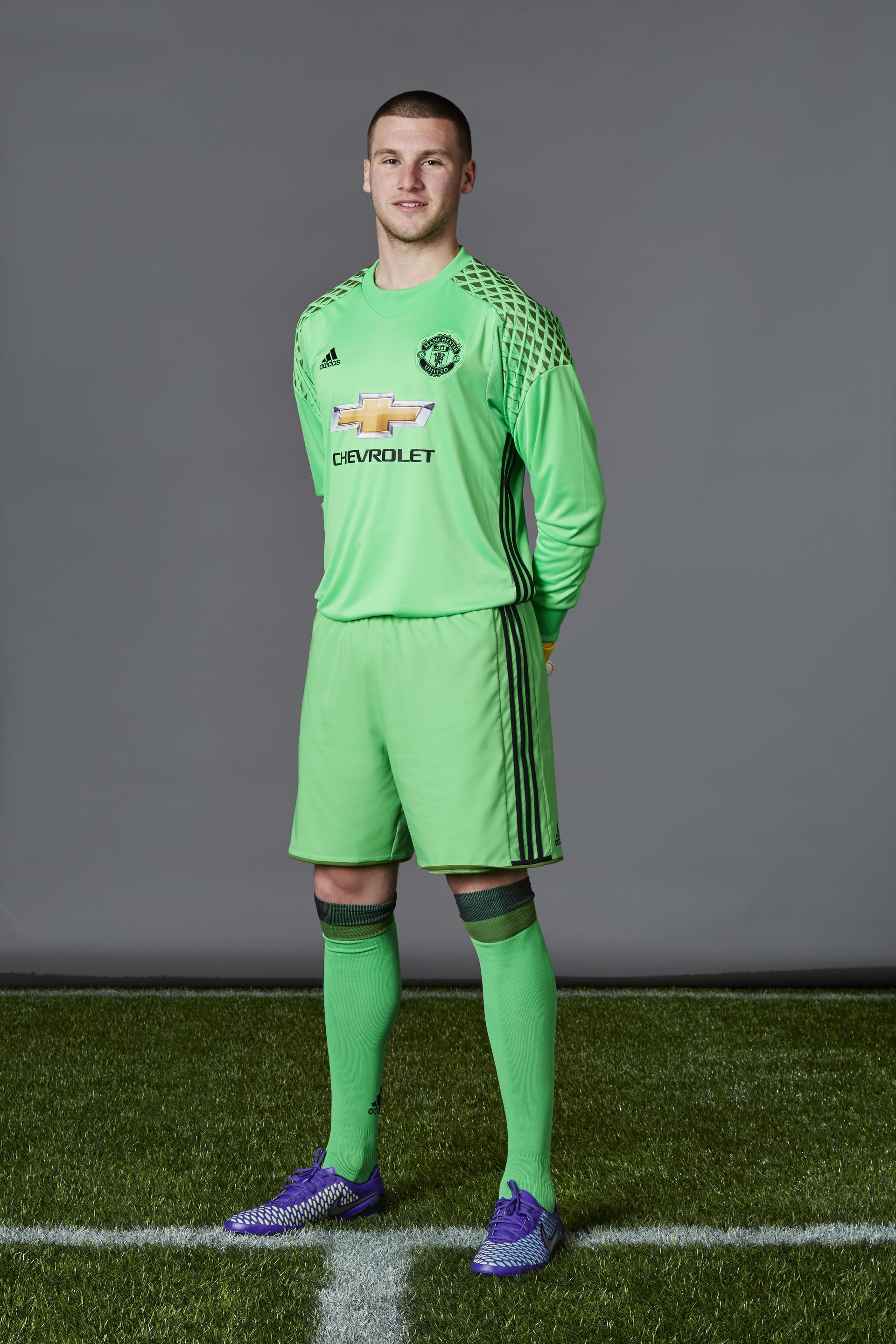 Sam Johnstone posing in his green United kit at a photoshoot.