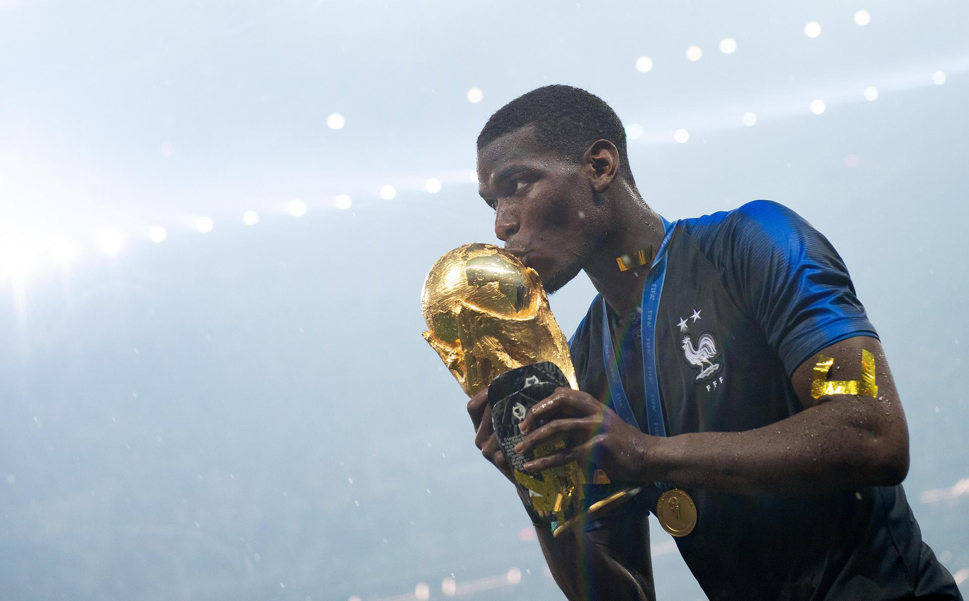 Paul Pogba holding the World Cup trophy.