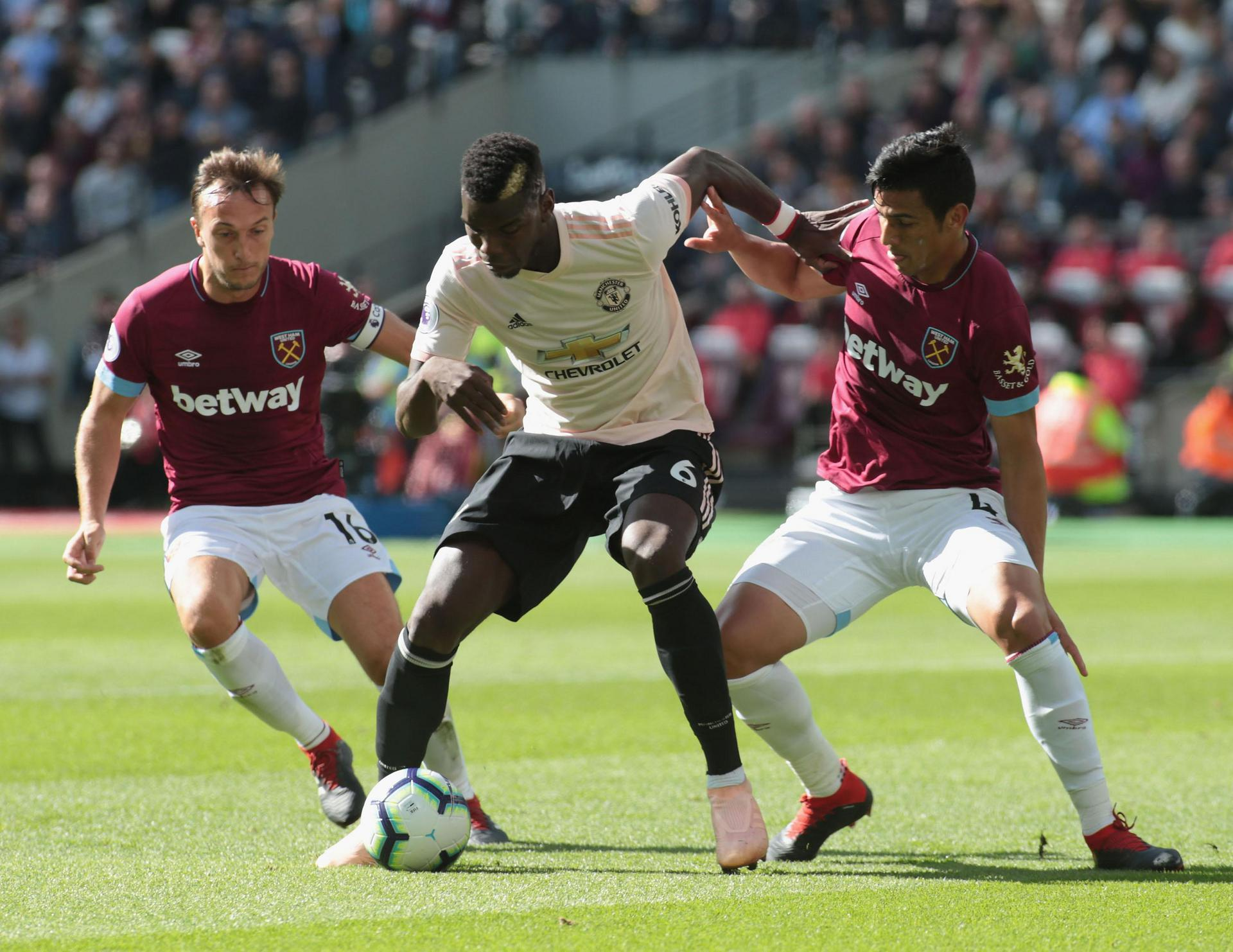 Paul Pogba battles for the ball with Mark Noble and Fabian Balbuena