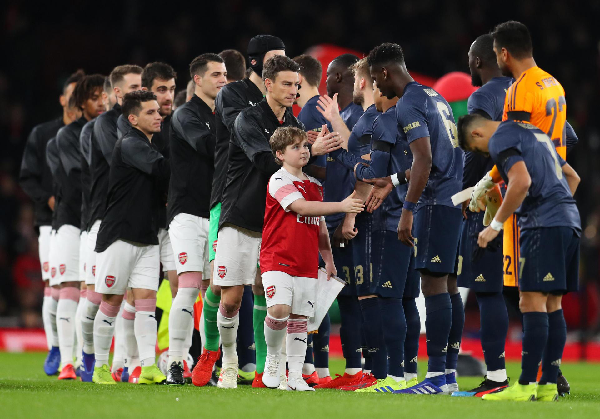 United and Arsenal players shake hands.