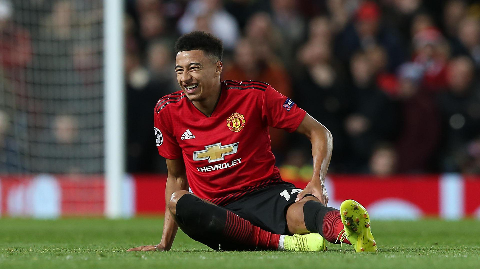 Jesse Lingard sits down in pain as half-time approaches.