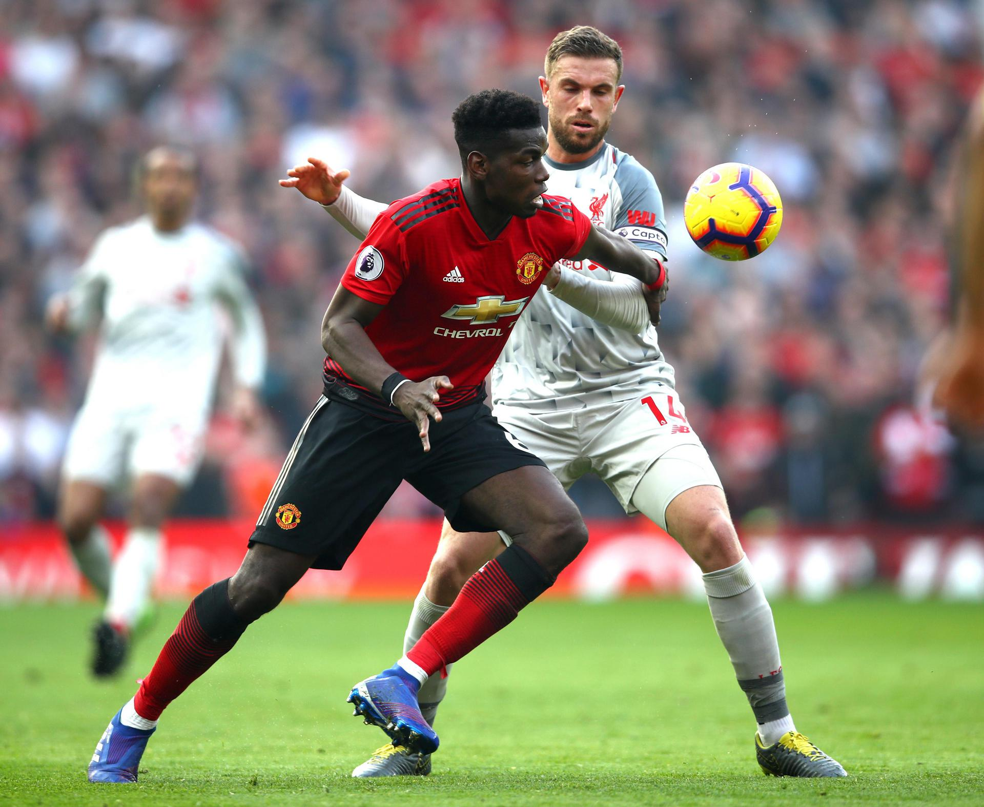 Paul Pogba beats Liverpool's Jordan Henderson to the ball at Old Trafford.