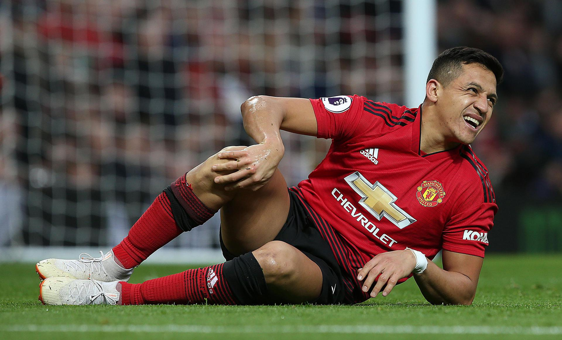 Alexis Sanchez winces in pain.