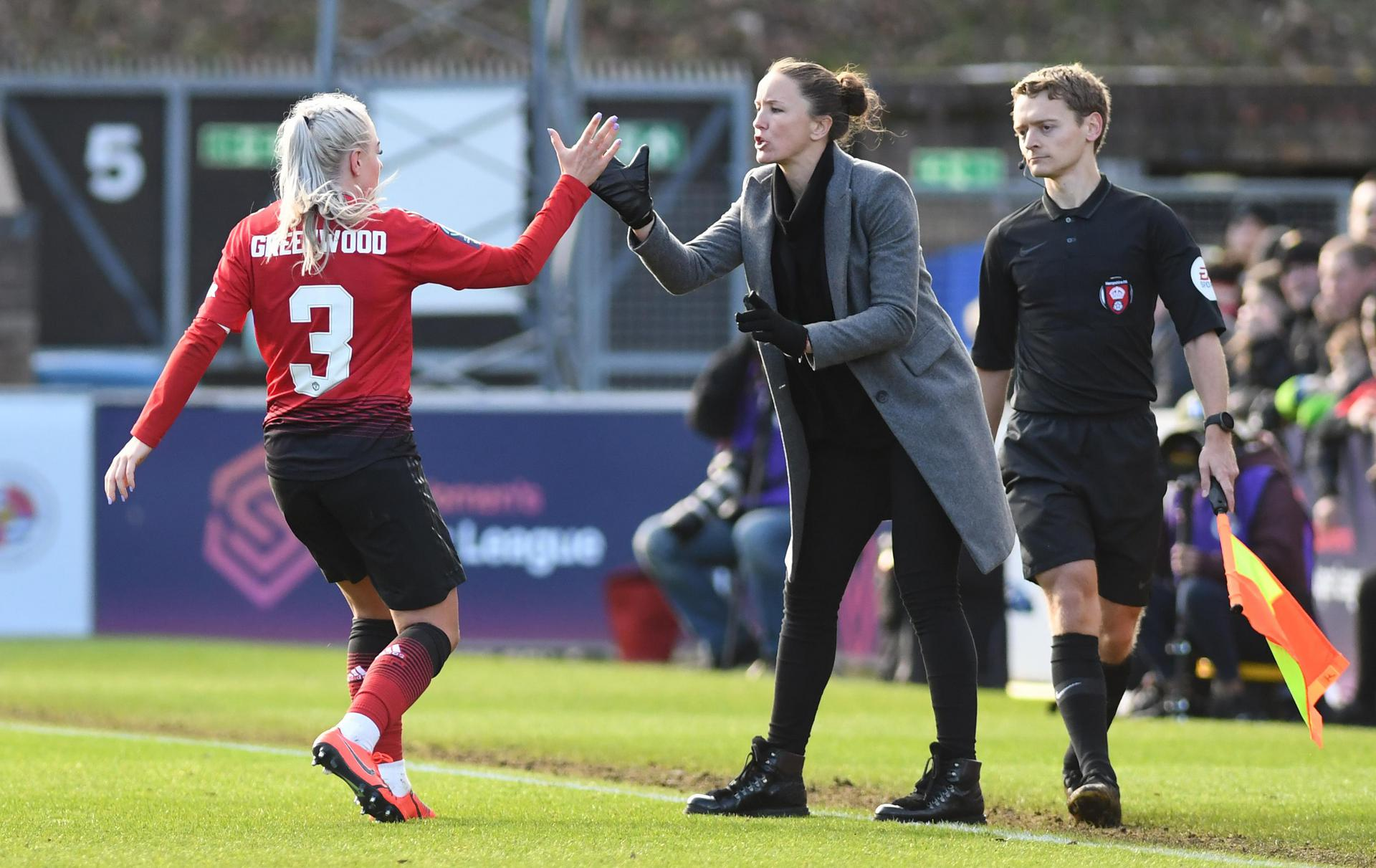 Casey Stoney shakes hands with Alex Greenwood.