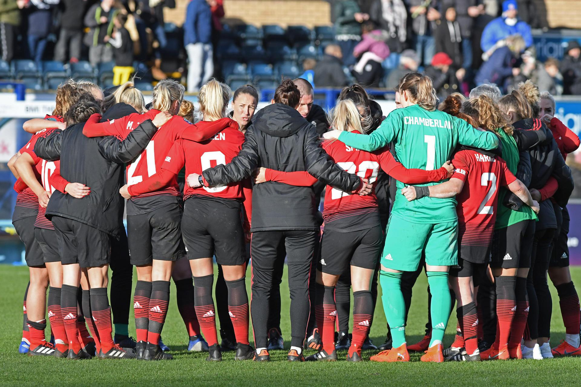Man United Women in a team huddle.