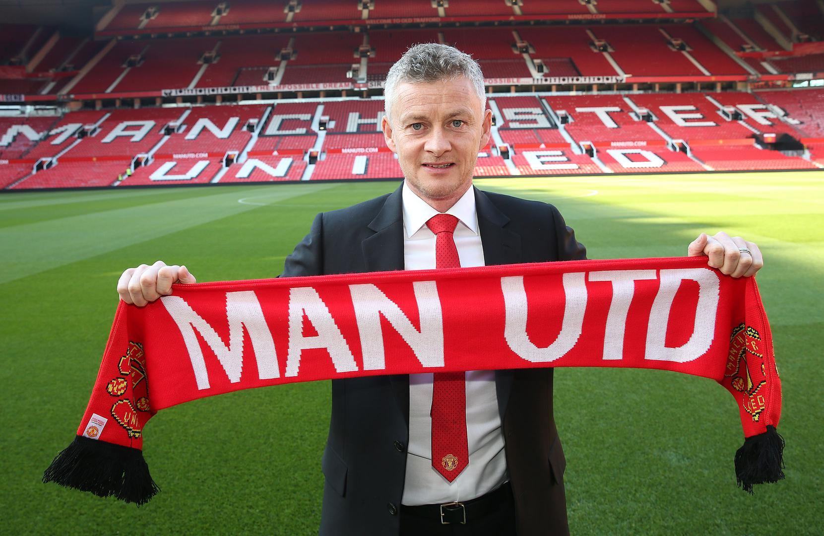 Ole Gunnar Solskjaer holds a Man Utd scarf after being appointed as permanent manager on 28 March 2019