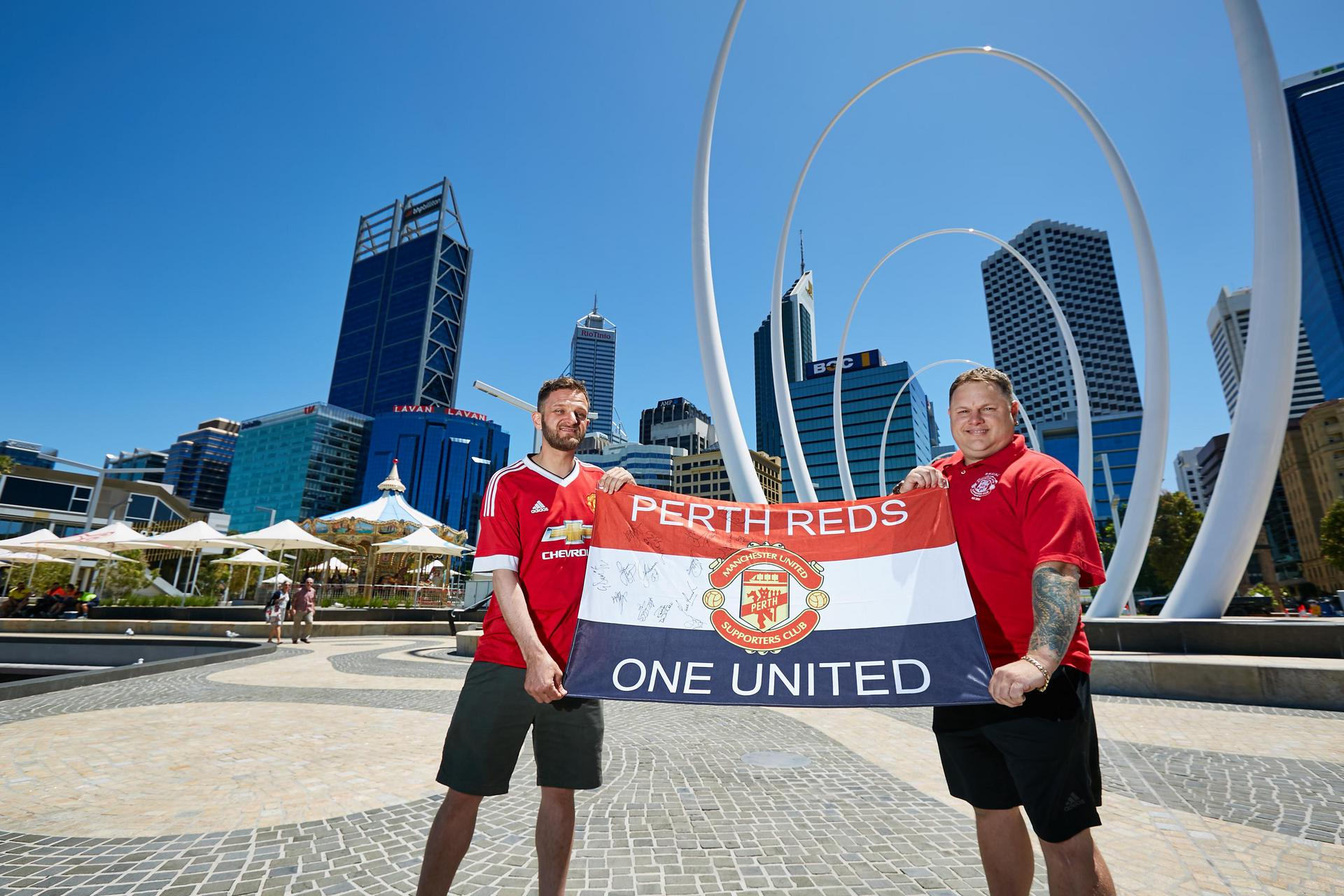 Two fans hold aloft a 'Perth Reds' flag
