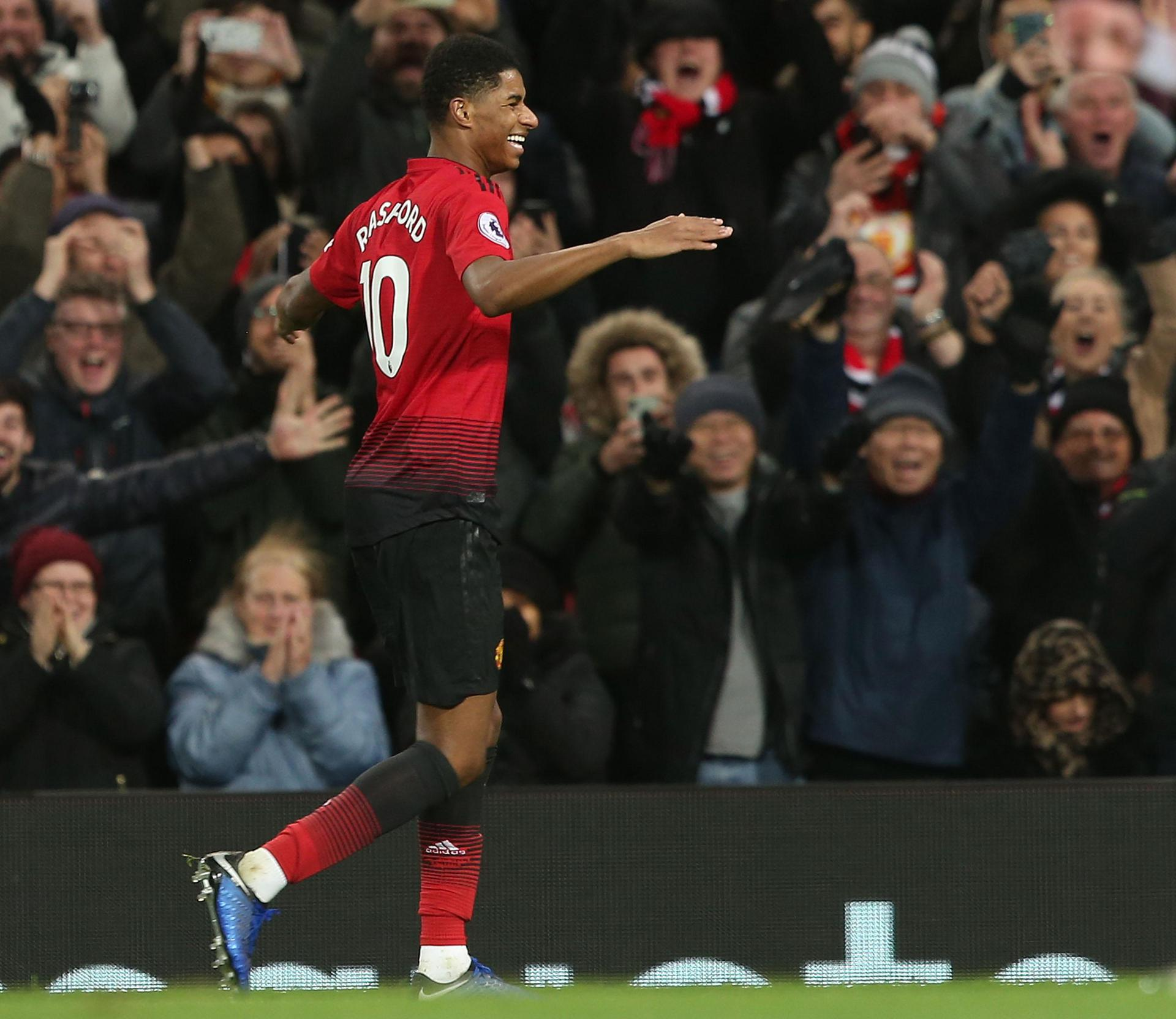 Marcus Rashford celebrates with the fans after scoring against Fulham