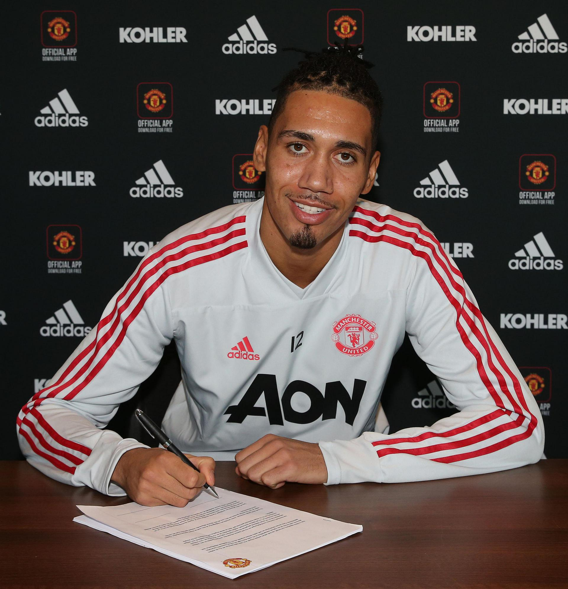 Chris Smalling signing his new contract with United.