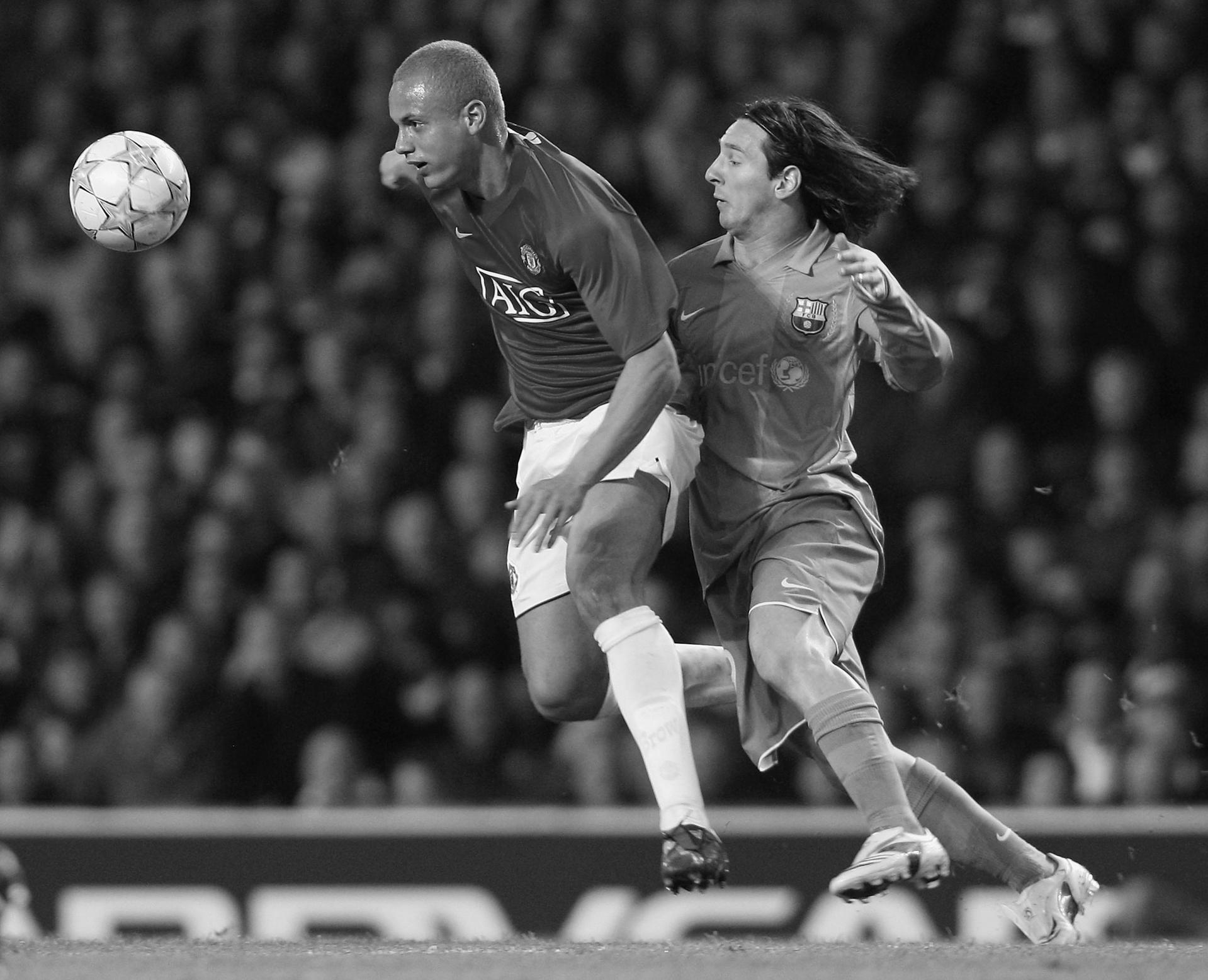 Wes Brown holds off Lionel Messi while chasing the ball.