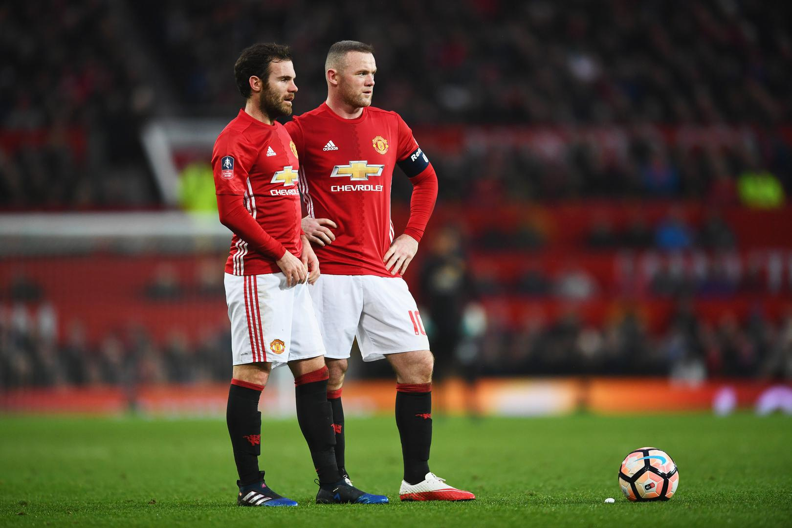 Juan Mata and Wayne Rooney stand over a free-kick during Manchester United's game against Wigan Athletic in 2017