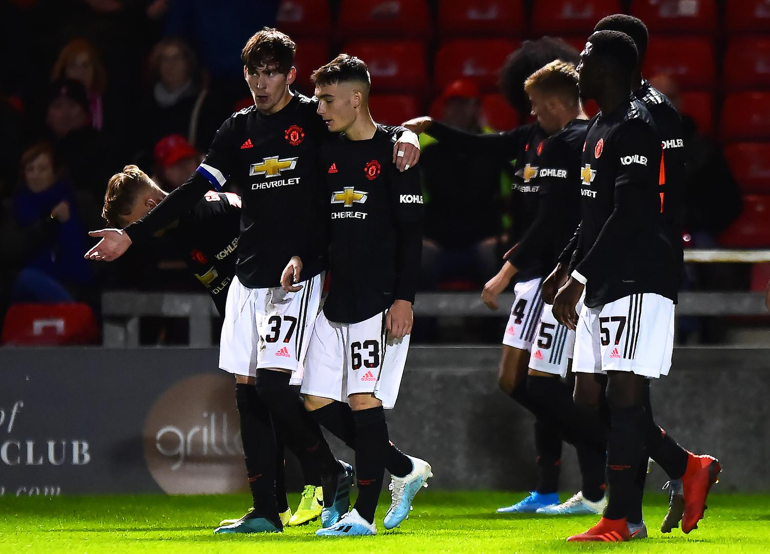 James Garner talks to his Manchester United Under-21 team-mates after scoring the winning goal at Lincoln City