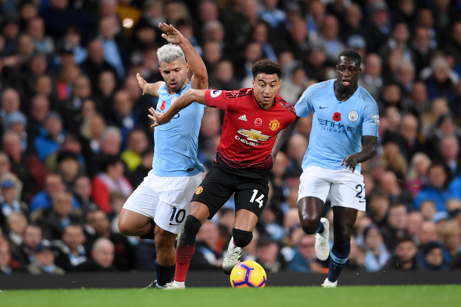 Jesse Lingard runs between Sergio Aguero and Benjamin Mendy.,