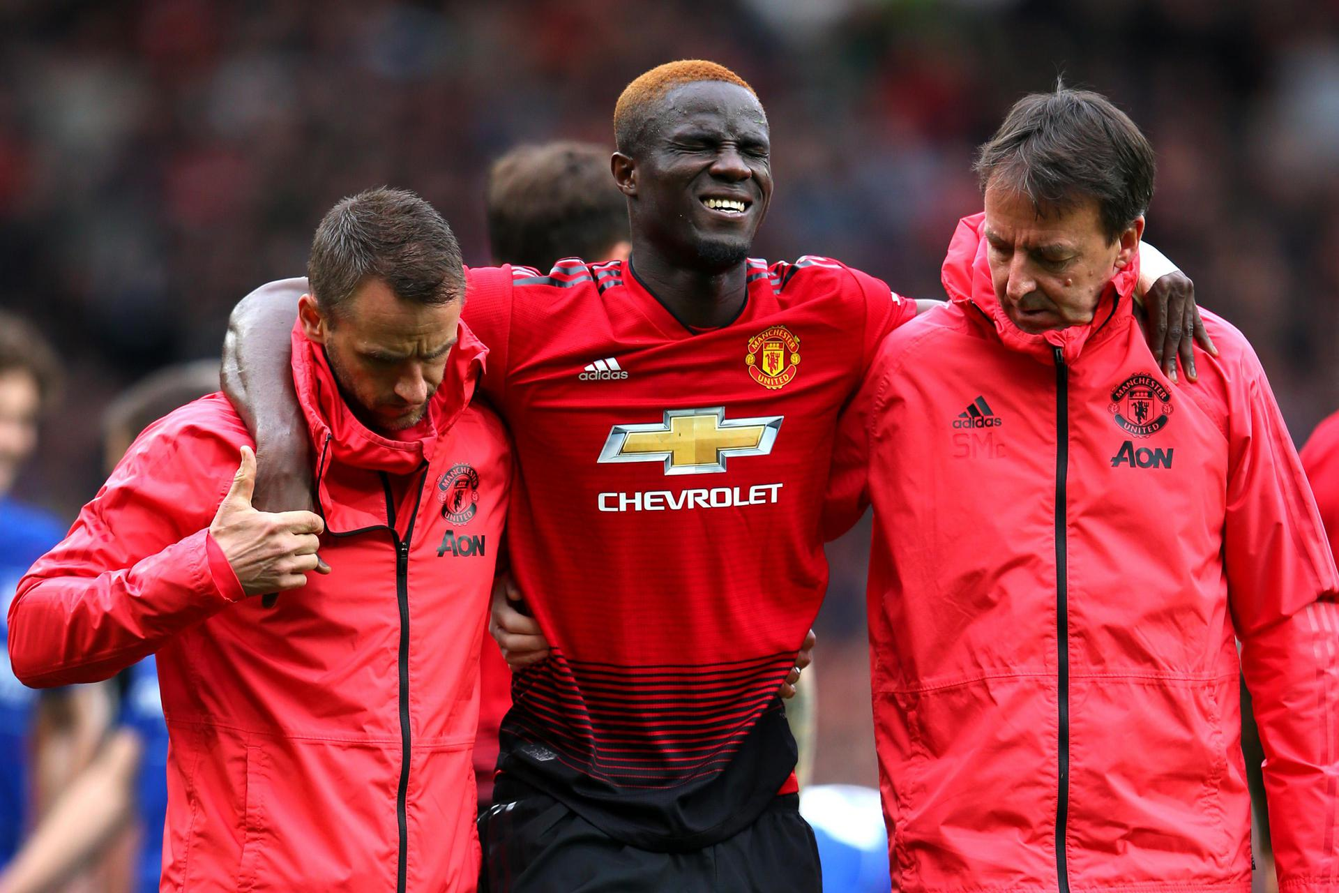Eric Bailly with his arm around two coaches.