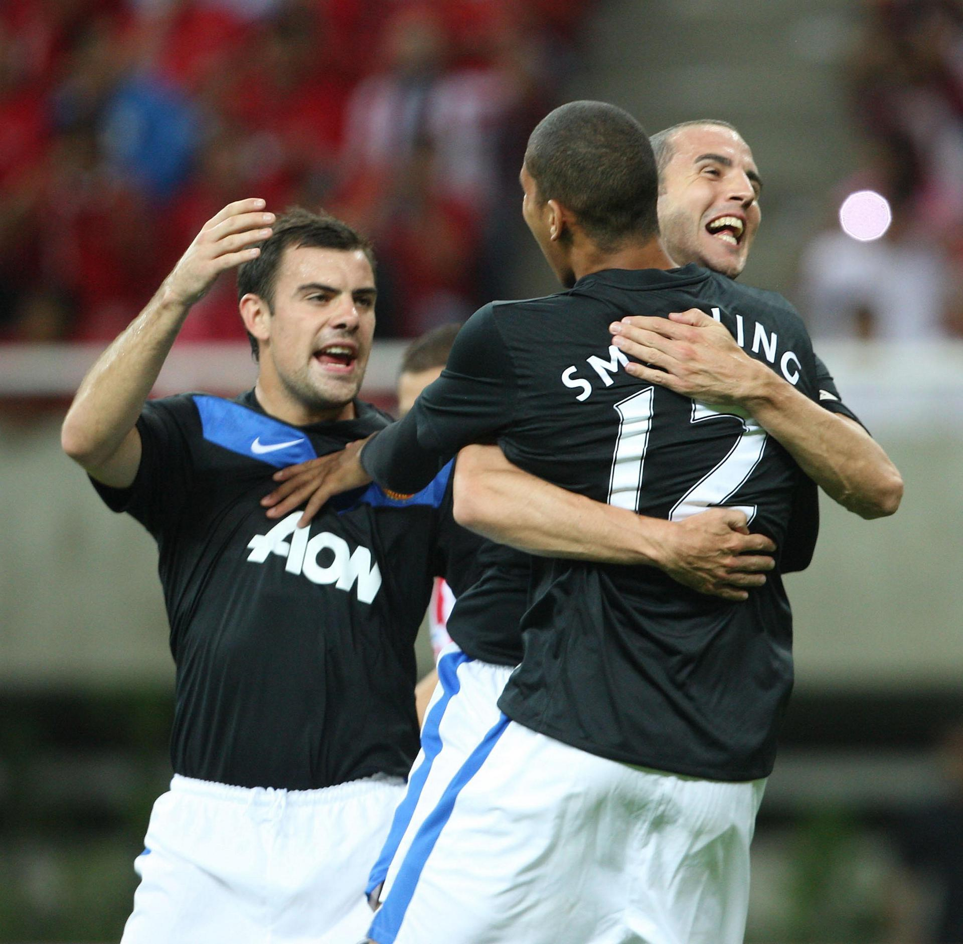 Chris Smalling is hugged by John O'Shea as Darron Gibson looks on.