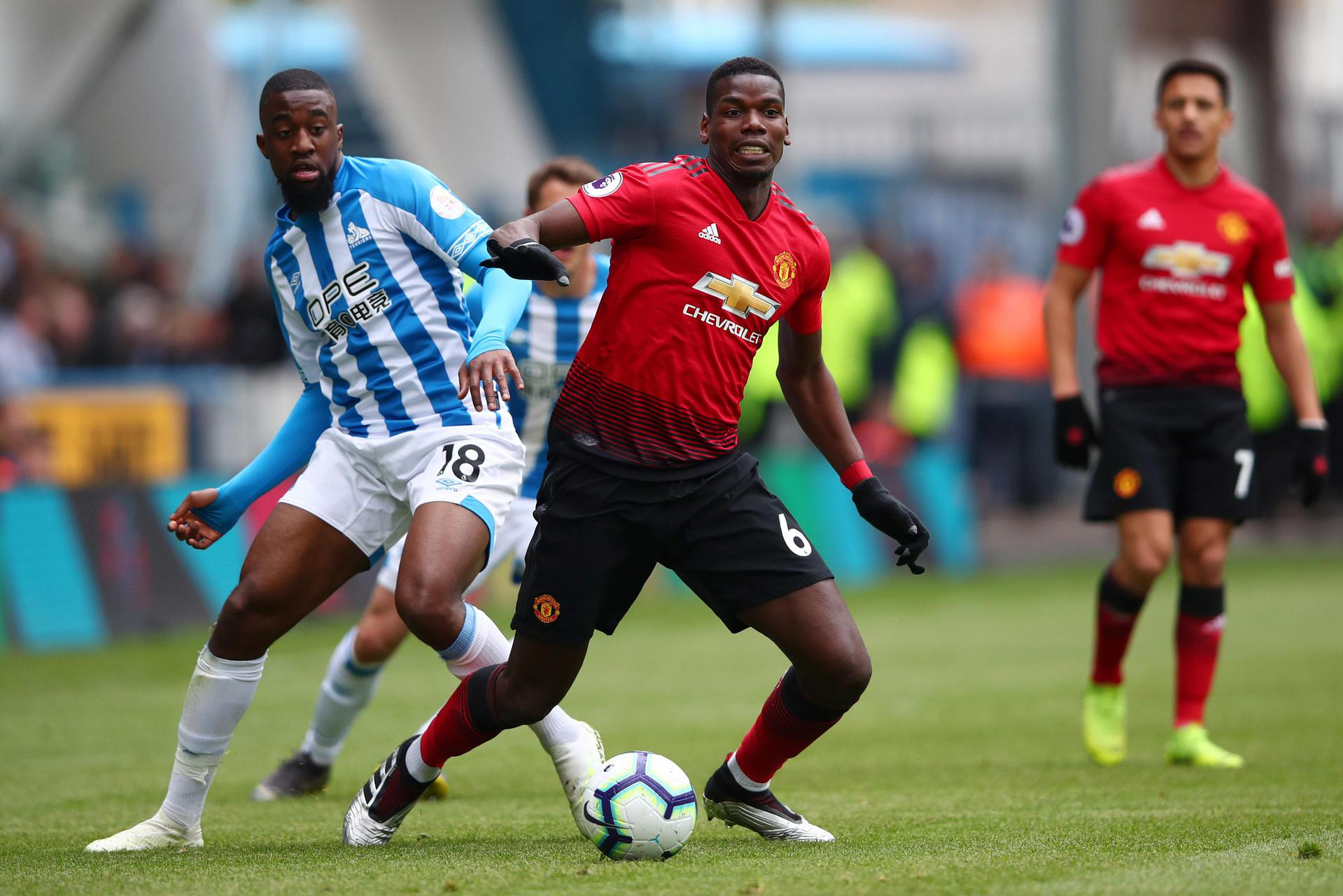 Paul Pogba battles with Huddersfield goalscorer Isaac Mbenza