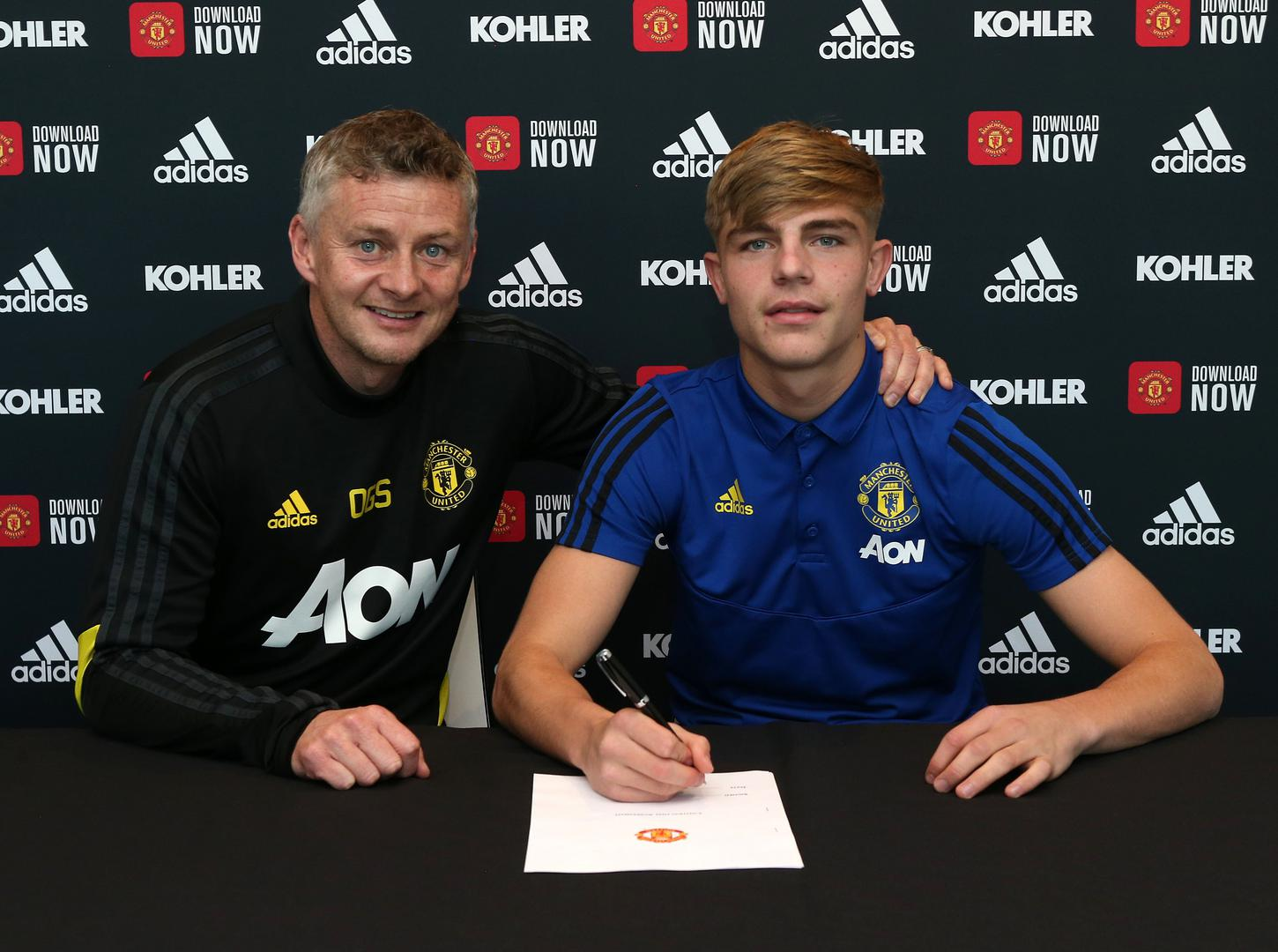 Brandon Williams, accompanied by first team manager Ole Gunnar Solskjaer, signs his new Manchester United contract.