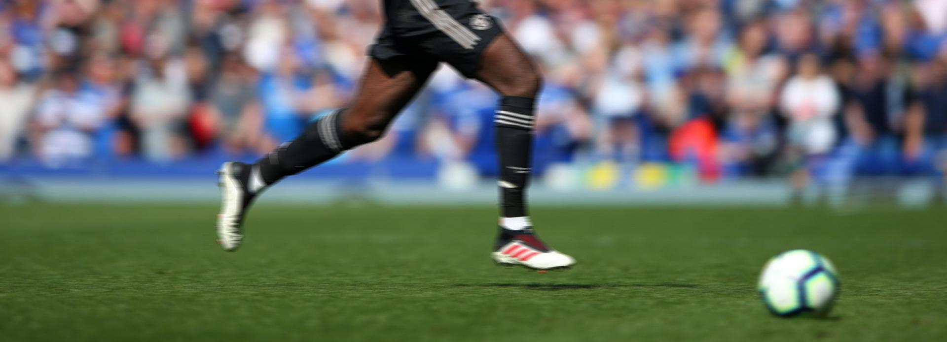 Close-up of Manchester United player's feet as he runs with the ball,