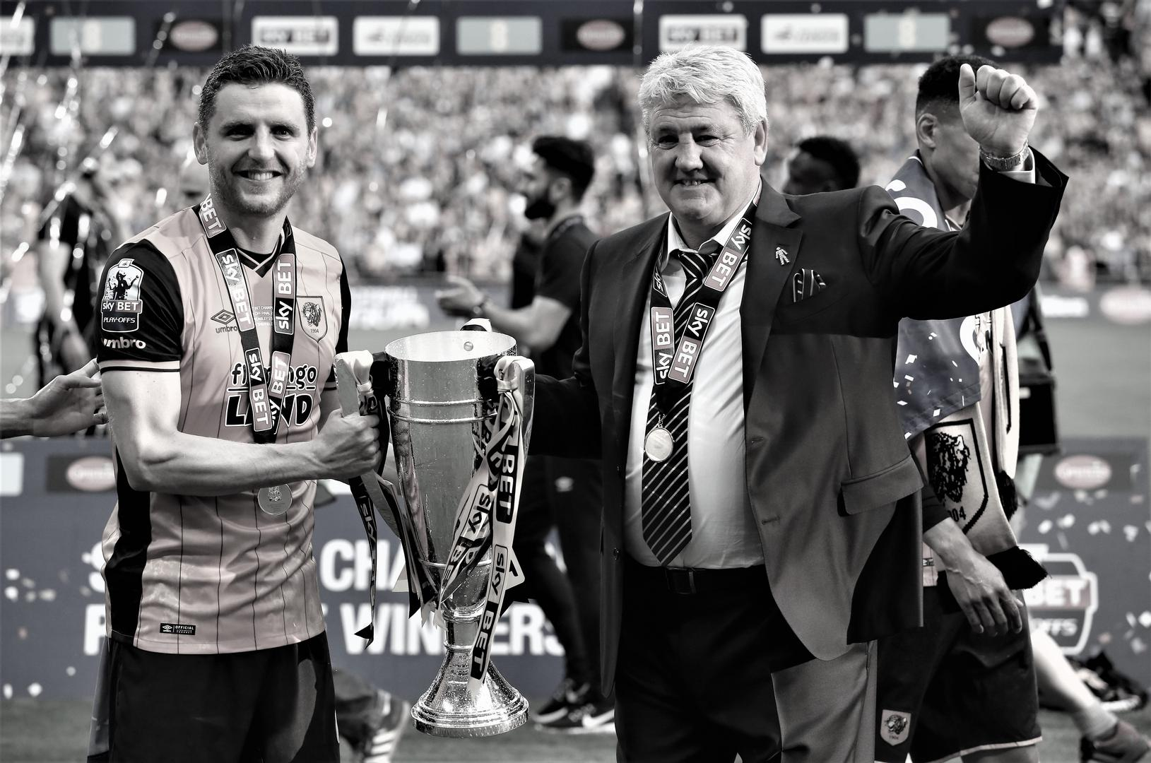 Alex Bruce and his dad Steve Bruce celebrate with the Championship play-off trophy after winning the final with Hull City