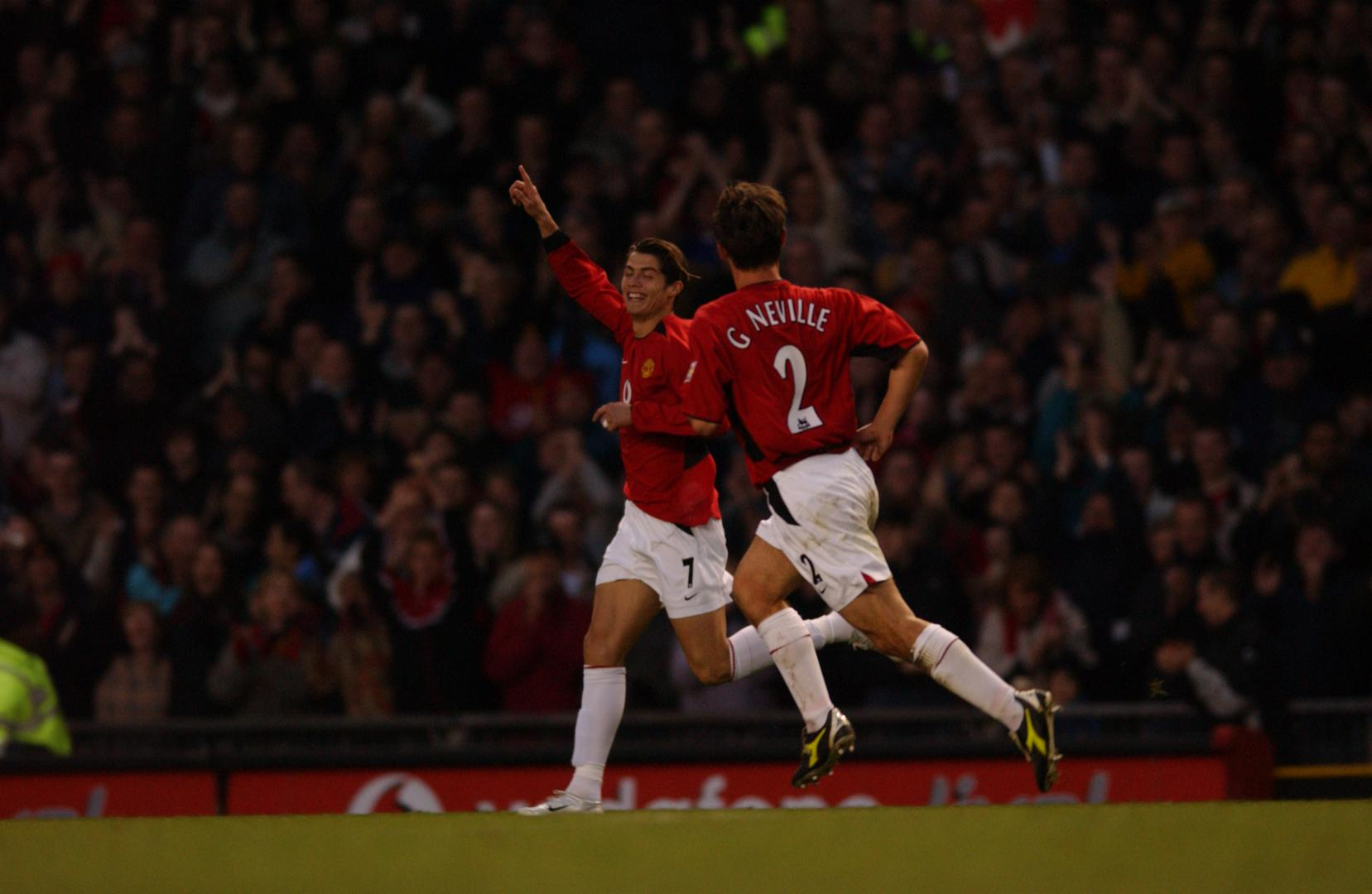 Cristiano Ronaldo celebrates his first goal for Manchester United with Gary Neville