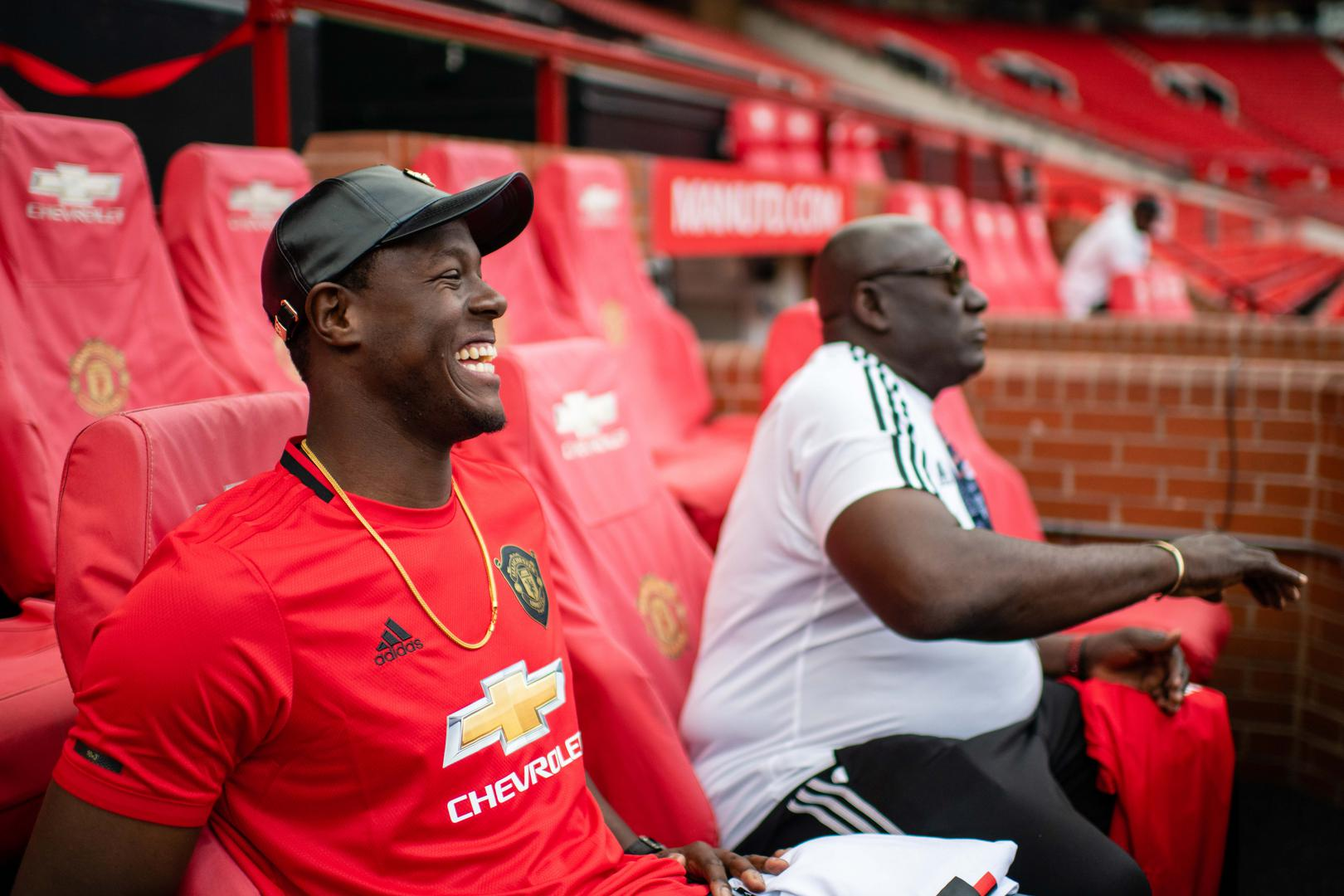 Carlos Brathwaite and Roddy Estwick sit in the Manchester United dugout during their tour of Old Trafford.
