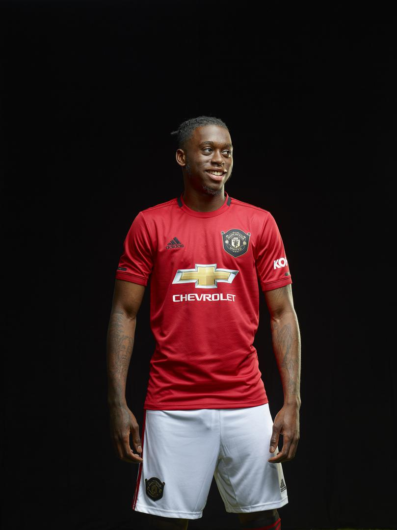 Aaron Wan-Bissaka smiles for the camera while wearing the new Manchester United home kit for 2019/20