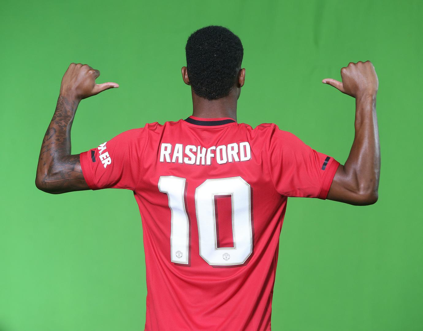 Marcus Rashford points to his name and shirt number.