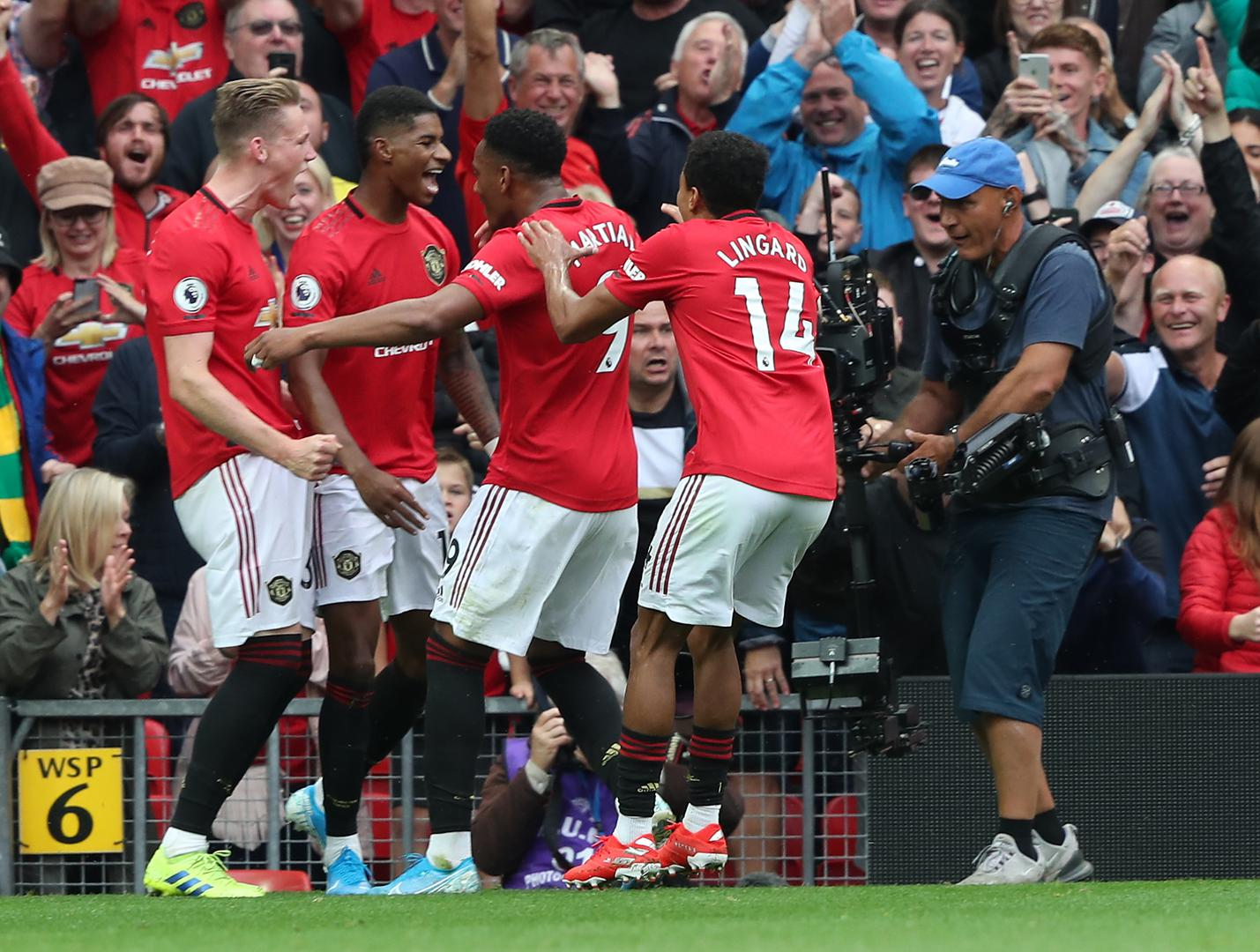 Marcus Rashford is mobbed after scoring his second goal.