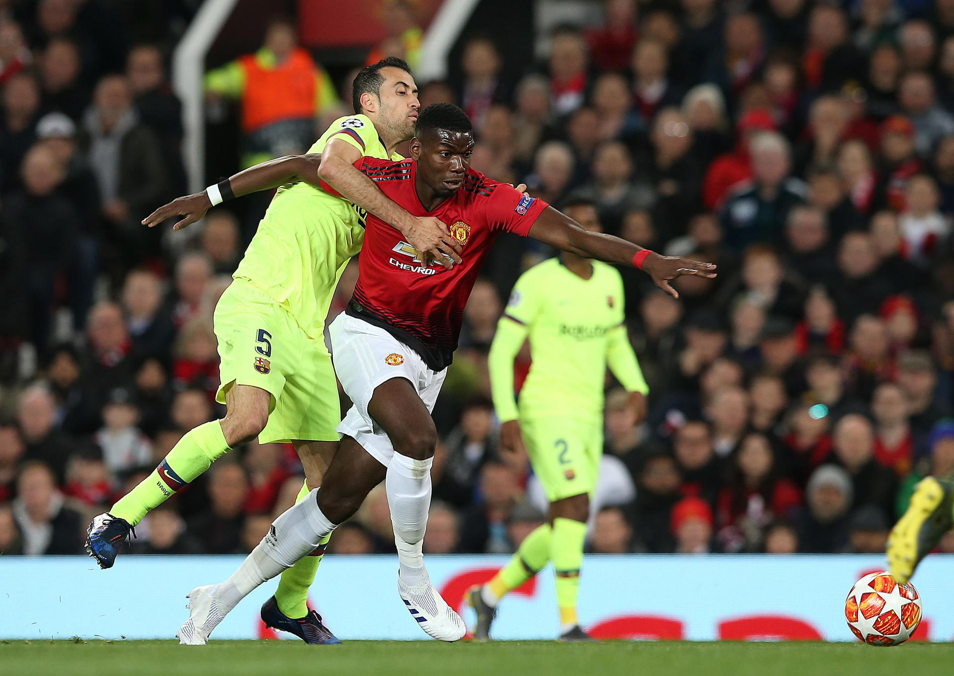 Paul Pogba shrugs off Sergio Busquets.