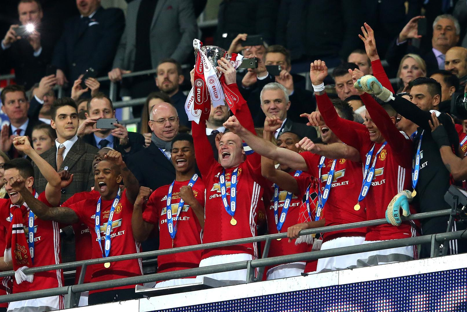 Wayne Rooney lifts the League Cup.