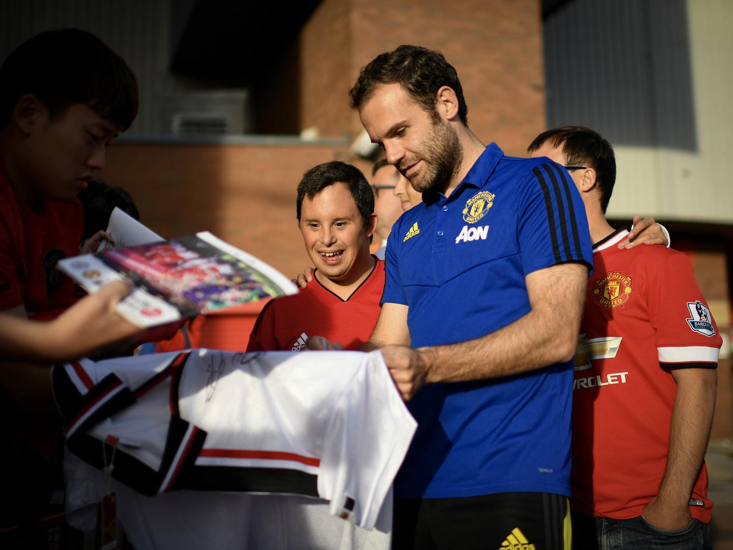 Juan Mata signs autographs for Manchester United supporters at Old Trafford