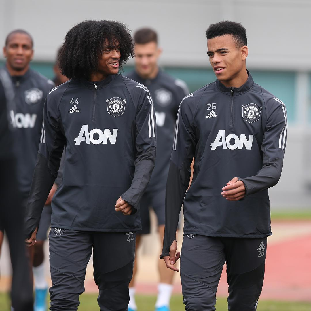 Tahith Chong and Mason Greenwood walk out for a first-team session at the Aon Training Complex