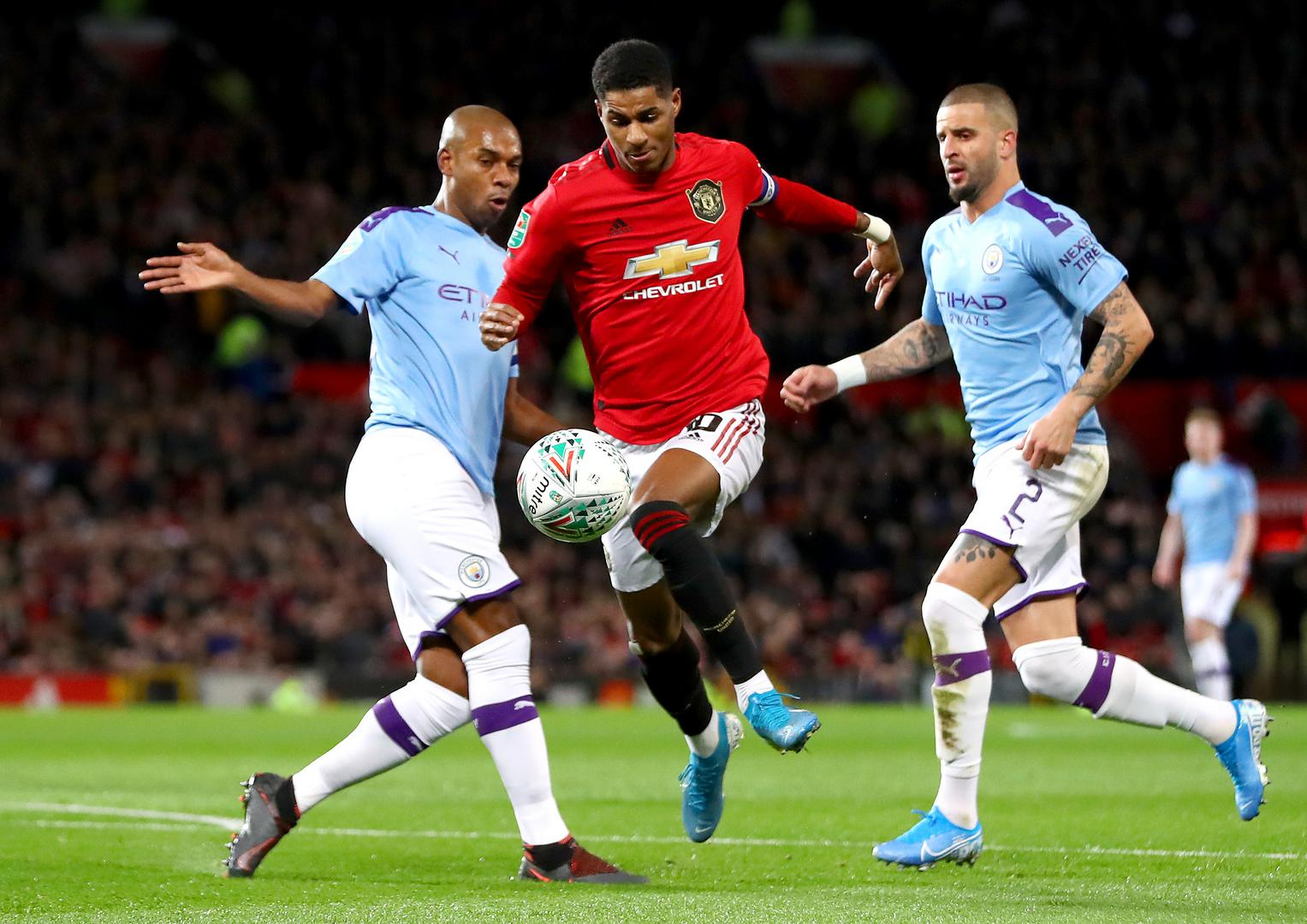 Marcus Rashford runs between two Manchester City defenders.