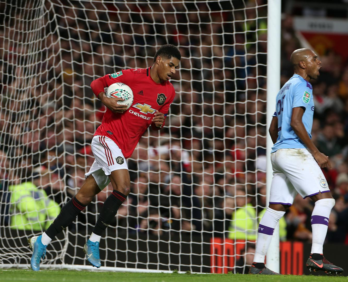 Marcus Rashford picks the ball out of the net after scoring against Man City.