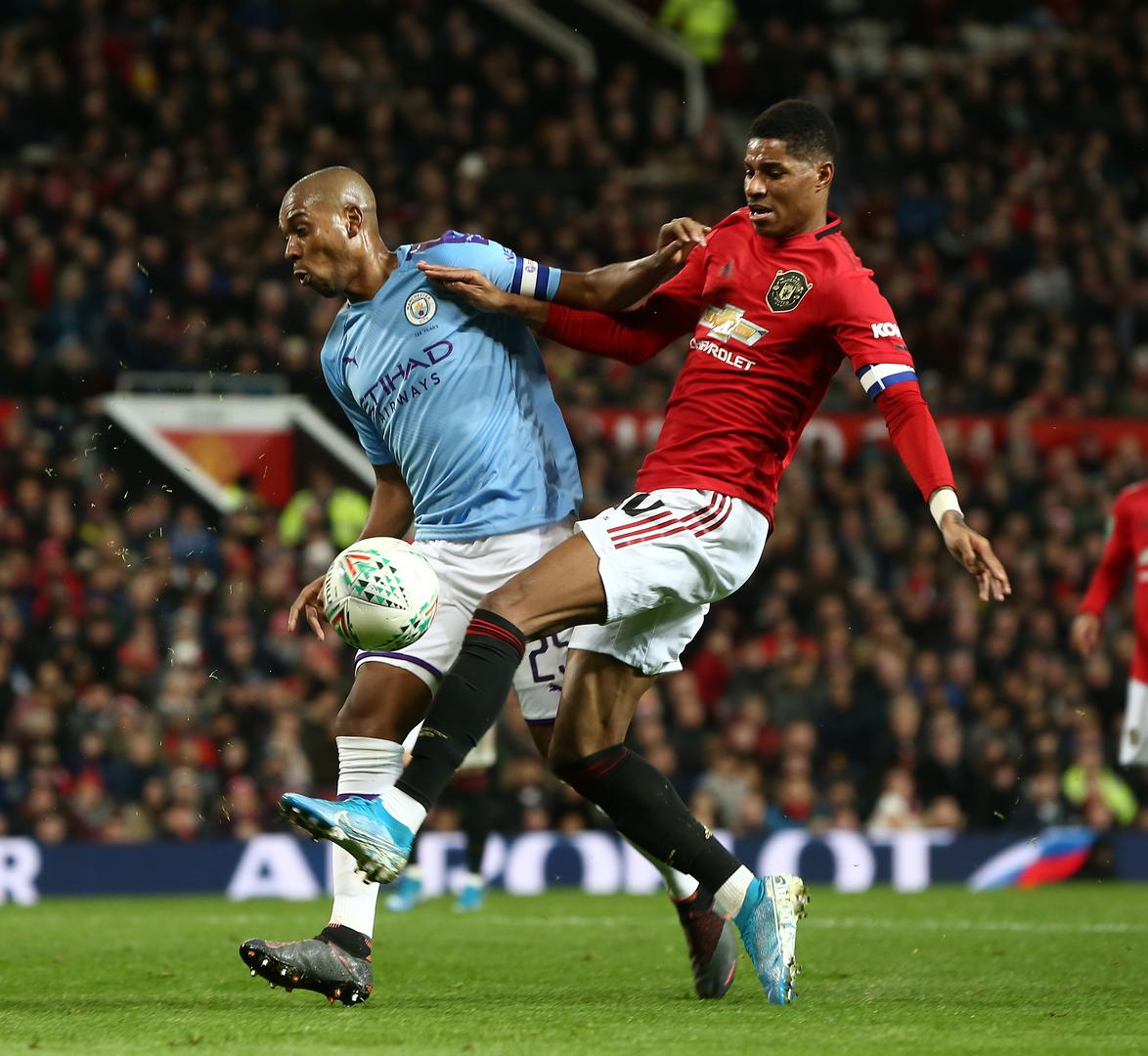 Marcus Rashford tries to shoot under pressure from Fernandinho