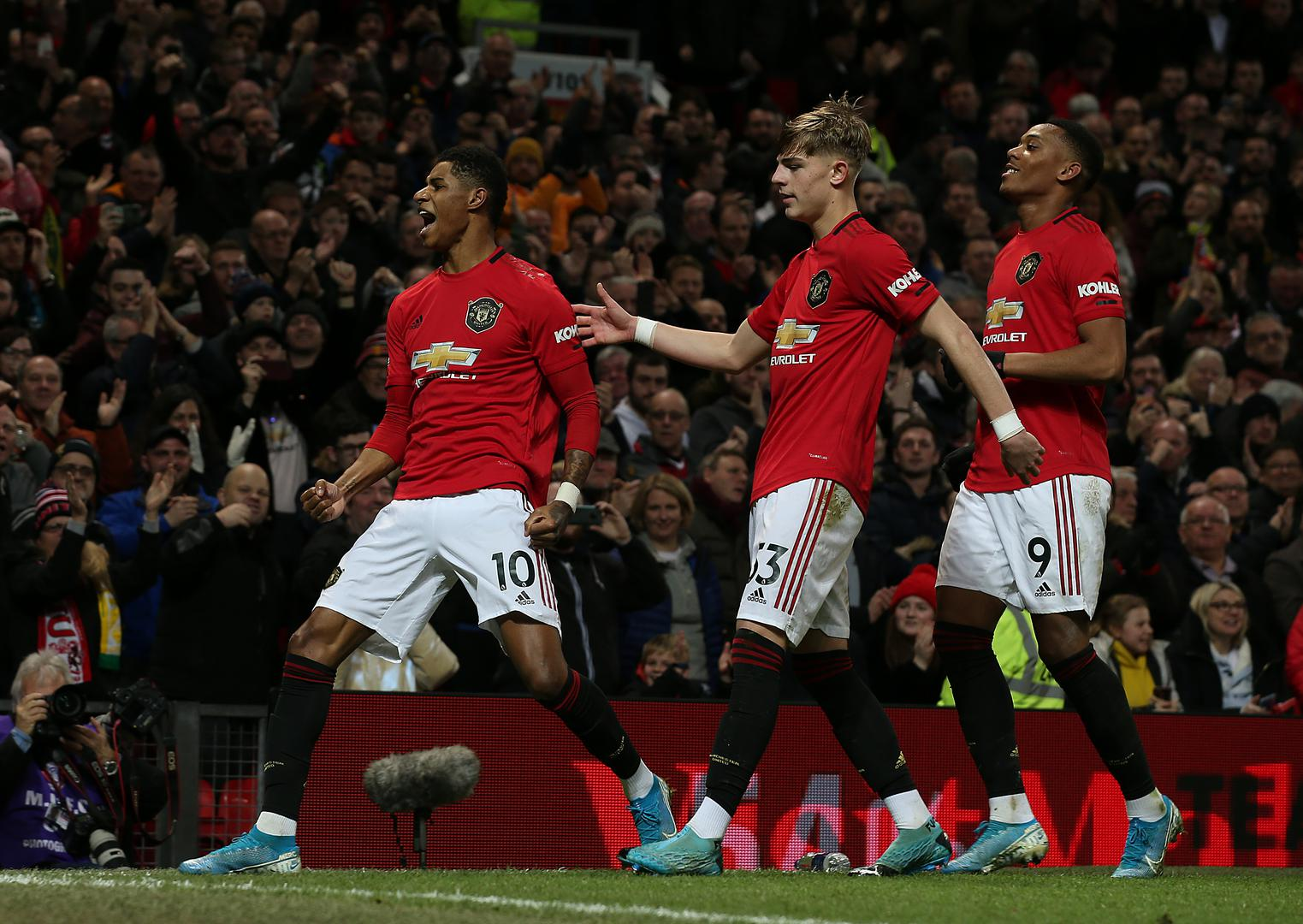Marcus Rashford celebrates in front of the Stretford End.