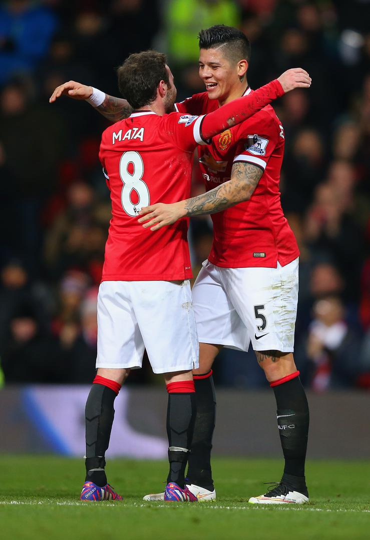 Juan Mata and Marcos Rojo celebrate a goal during the FA Cup replay win over Cambridge United at Old Trafford in February 2015