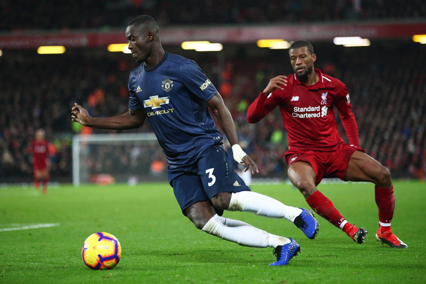 Eric Bailly on the ball for Manchester United at Anfield, watched by Georginio Wijnaldum