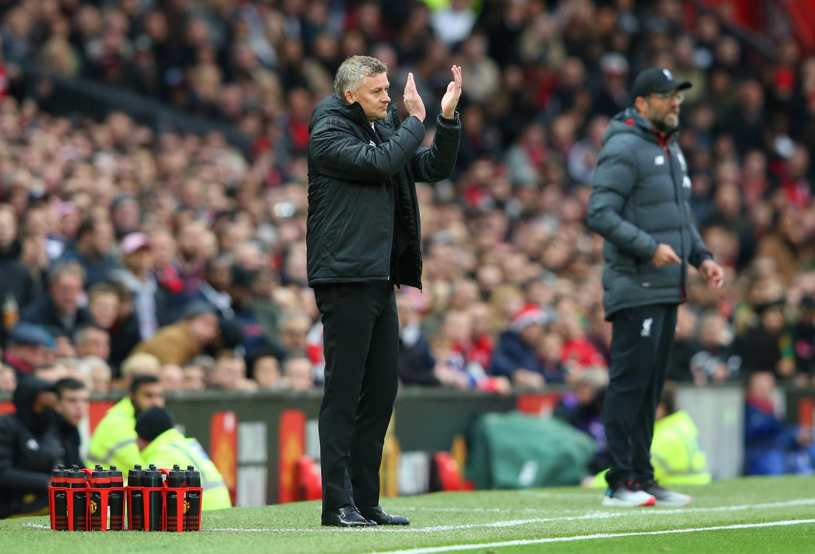 Ole Gunnar Solskjaer claps as Jurgen Klopp stands in the background