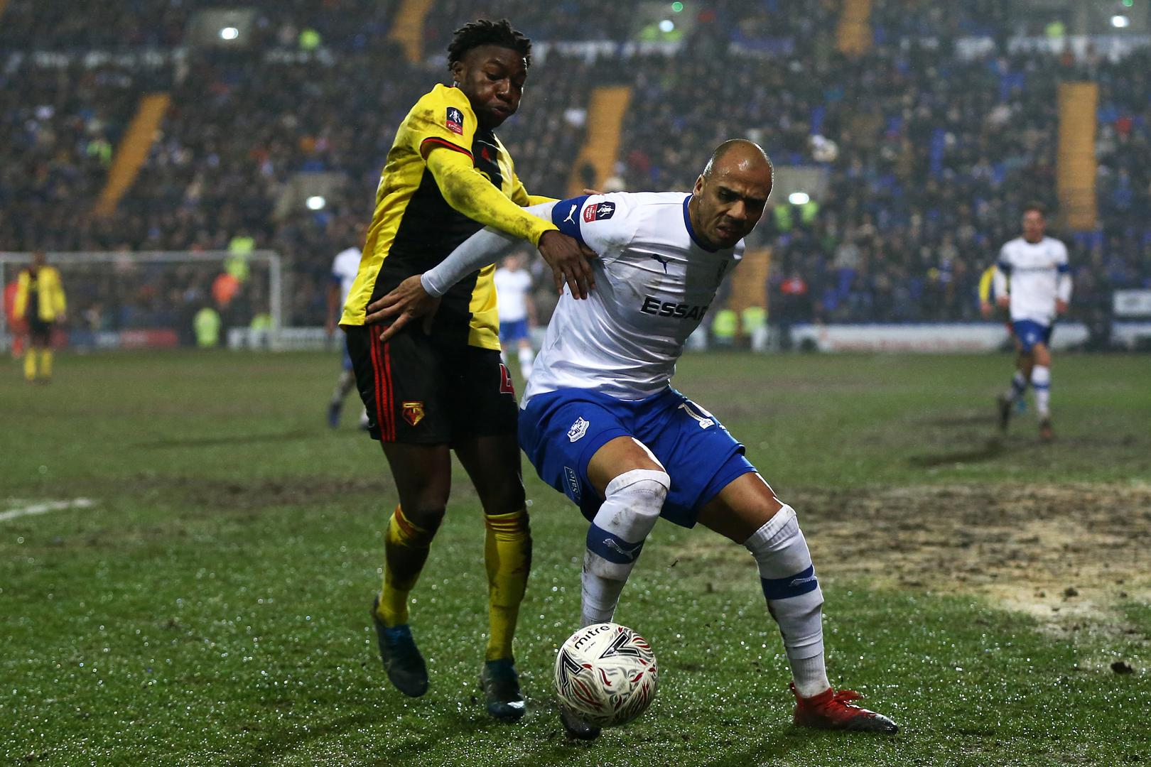 A Tranmere Rovers player holds off a Watford opponent during the FA Cup.