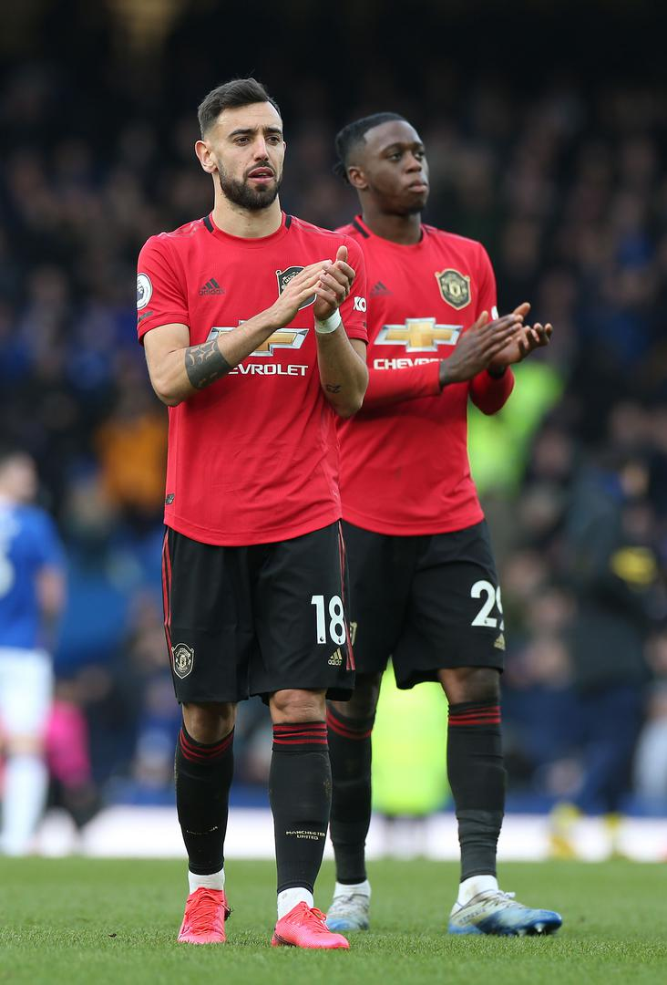 Bruno Fernandes and Aaron Wan-Bissaka applaud the visiting Man Utd supporters.