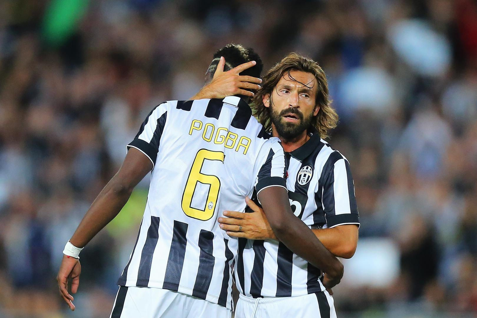 Paul Pogba is hugged by Andrea Pirlo.,