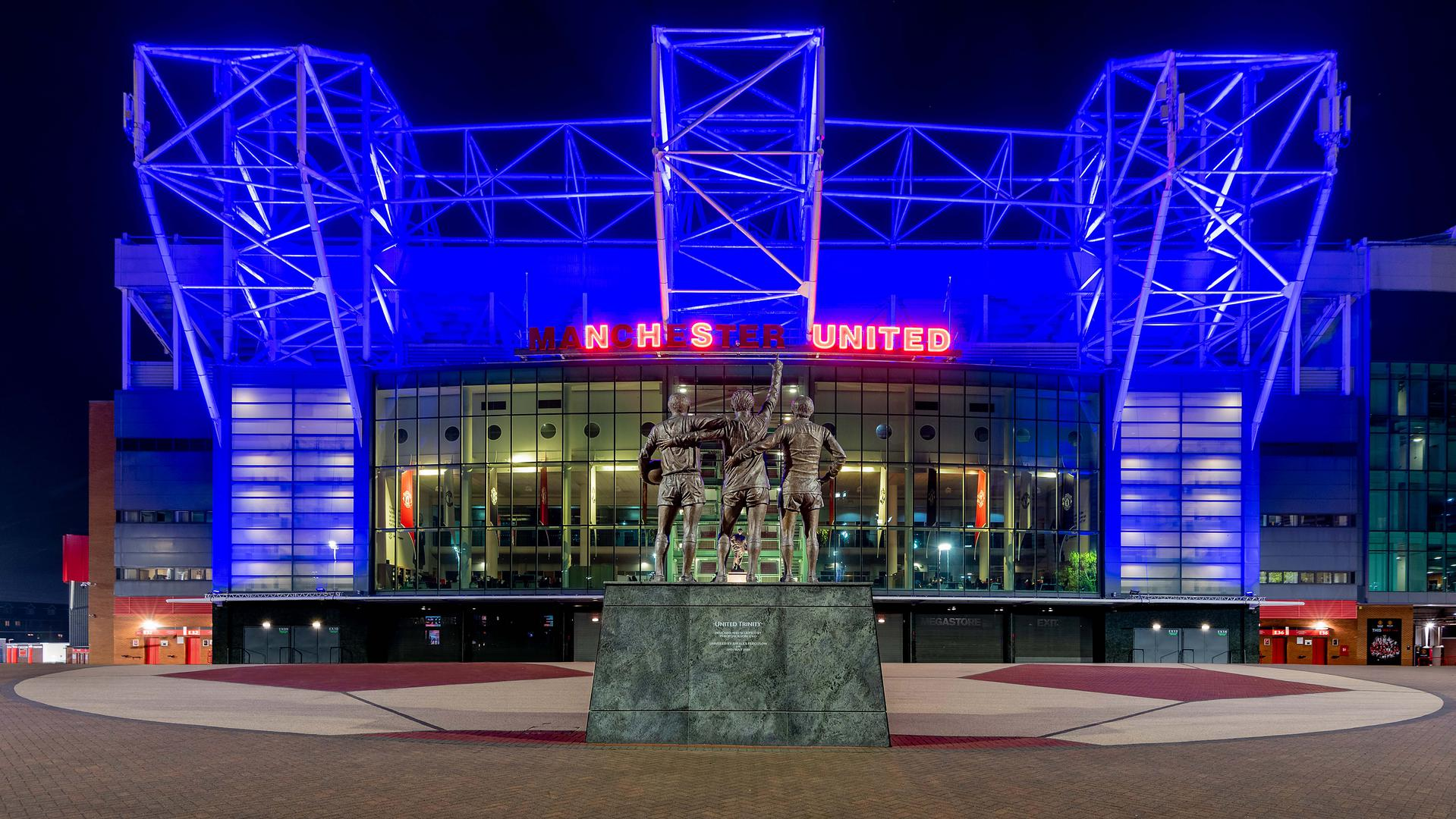 Old Trafford lit up in blue with the neon sign spelling out NHS United.