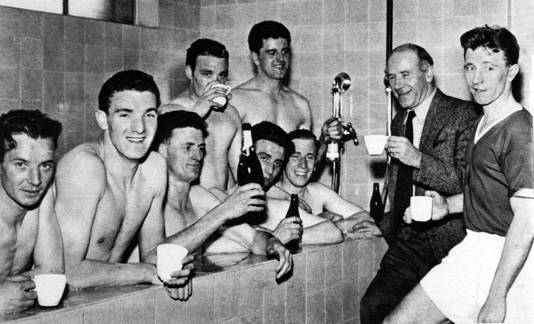 Manchester United players celebrate in the bath, with manager Matt Busby and captain Roger Byrne, after winning the 1956/57 league title