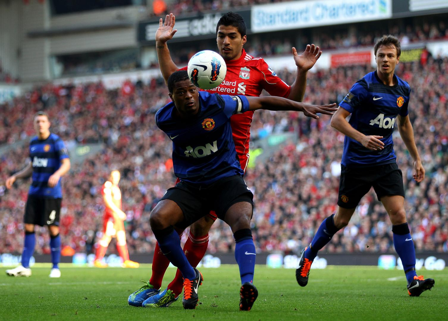 Patrice Evra is challenged by Luis Suarez