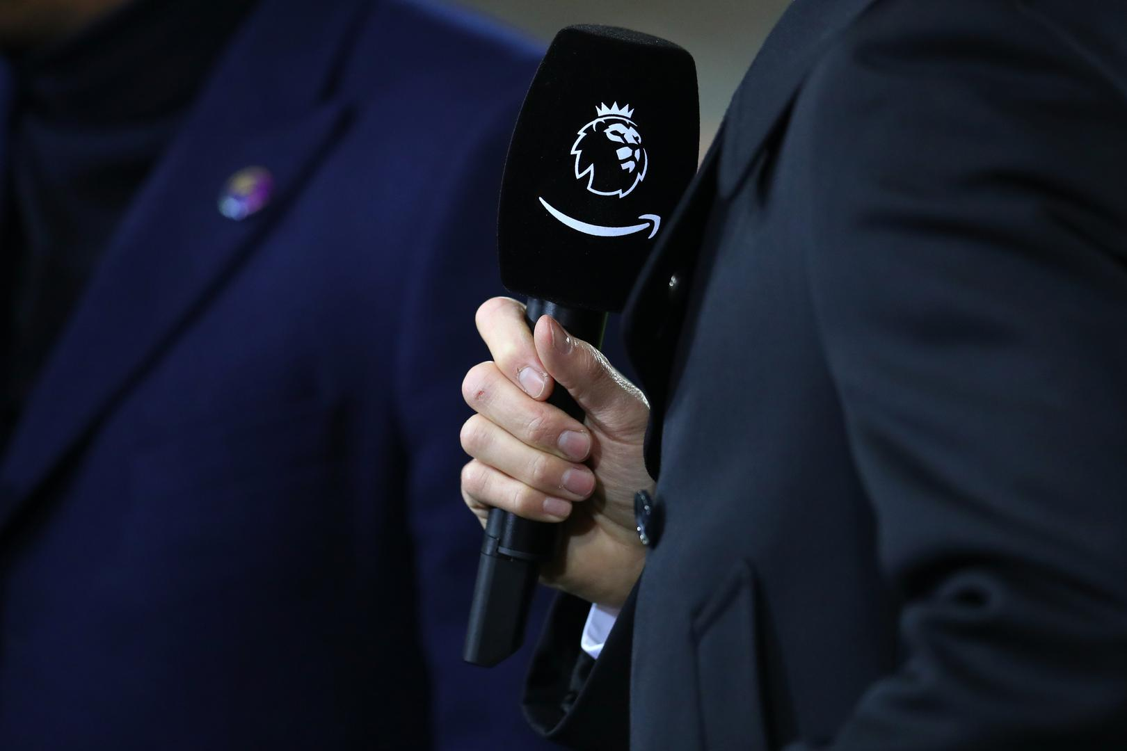 A close-up of a Premier League-branded microphone held by a TV reporter