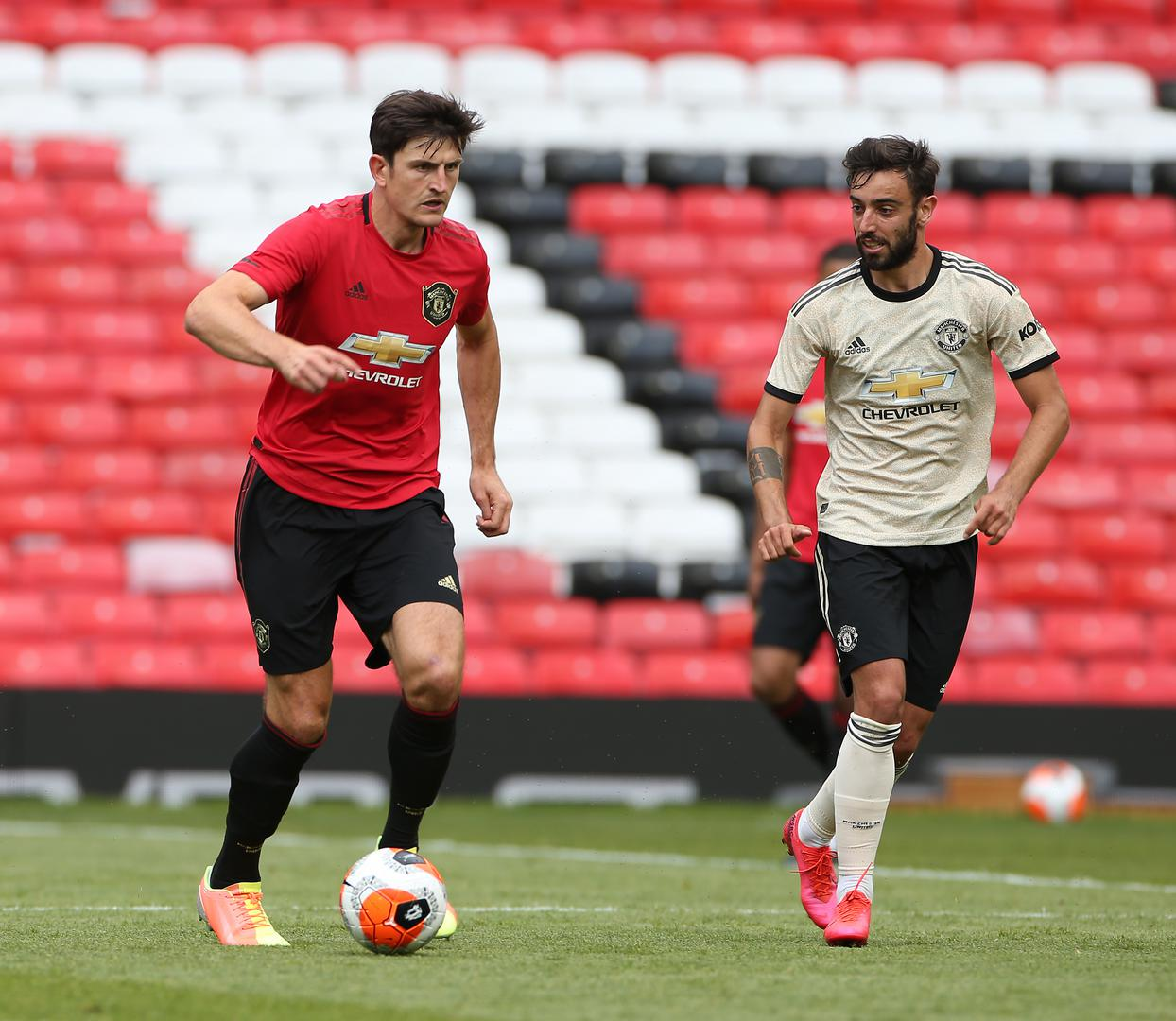 Harry Maguire on the ball, watched by Bruno Fernandes
