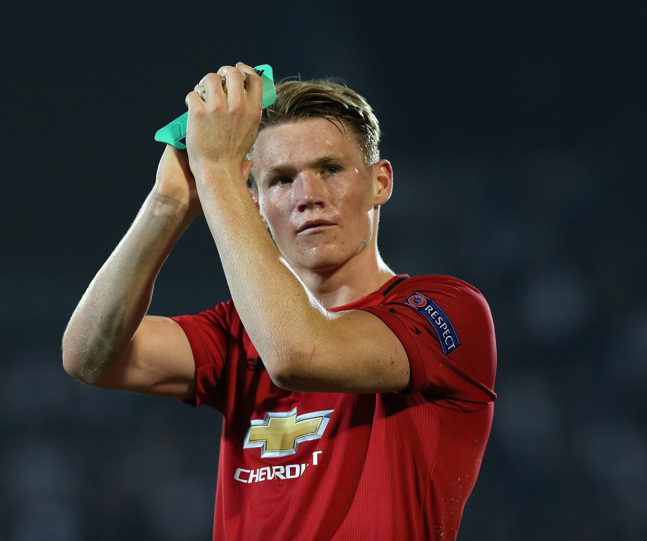 Scott McTominay applauds the travelling supporters.